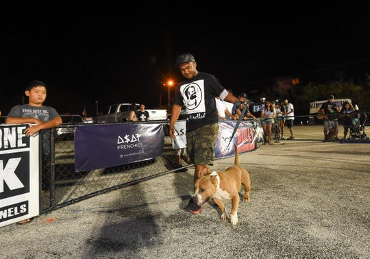 Rossal Hunt guides his dog Foster in the ABKC American Bully Dog Show during the 39th Annual APL Smokin' Wheels at the Guam International Raceway on April 12, 2019.
