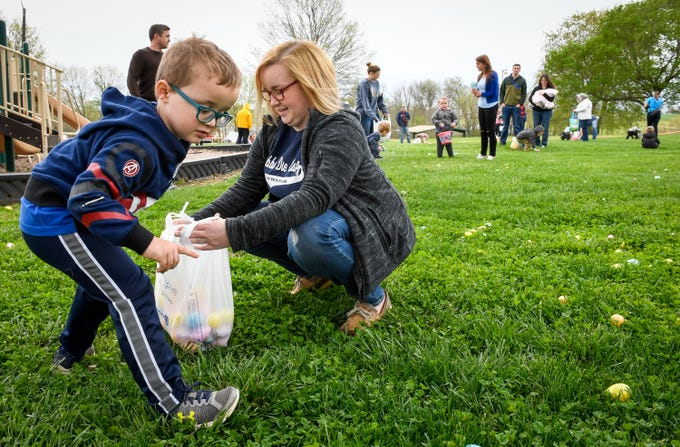 Gabe Townsend, four years-old, scrambles for eggs while his mother Stefani Lance holds the stash as children scramble for the more than 15,000 eggs hidden away in Community Park for the City of Henderson Parks and Recreation Department's annual Easter Egg Hunt Saturday, April 13, 2019.
