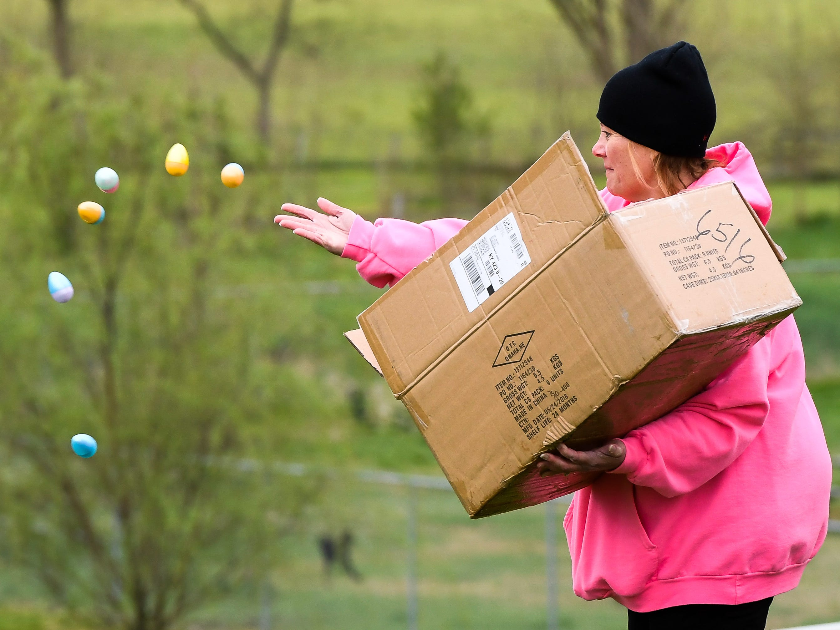Beth Austin, with the parks department, helps distribute some of the more than 15,000 eggs to be hidden away in Community Park for the City of Henderson Parks and Recreation Department's annual Easter Egg Hunt Saturday, April 13, 2019.