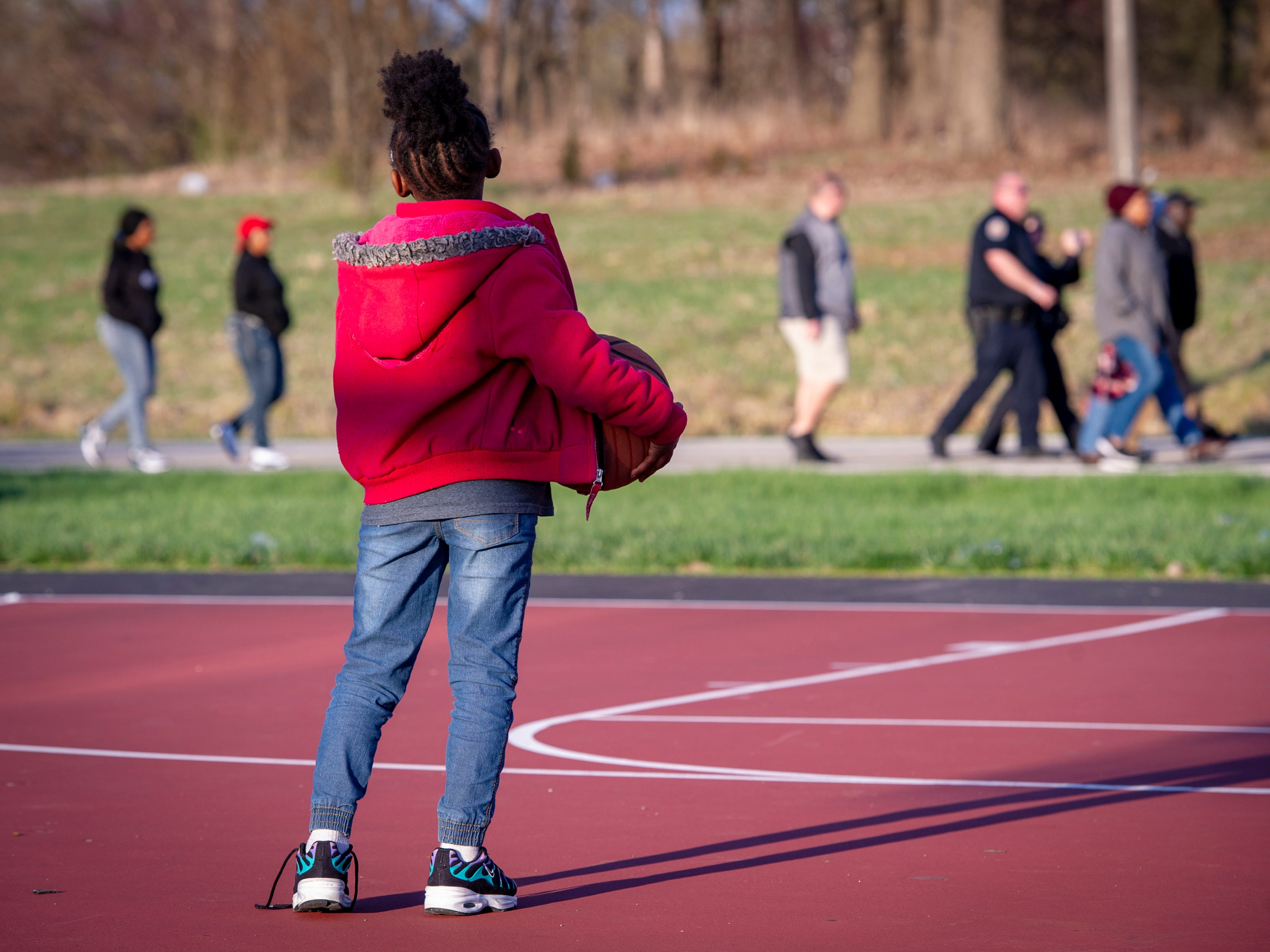 A young girl pauses her basketball game to watch the parade of activists pass by in the park. The Indianapolis Fraternal Order of Police, along with members of the Indy Ten Point Coalition, law enforcement officers from Southport, Lawrence, Cumberland police departments and a group of citizens participated in a peace walk, Friday, April 12, 2019. The groups organized in an effort to raise awareness for the increase of violence in the area of Washington Park on the northeast side of Indianapolis.