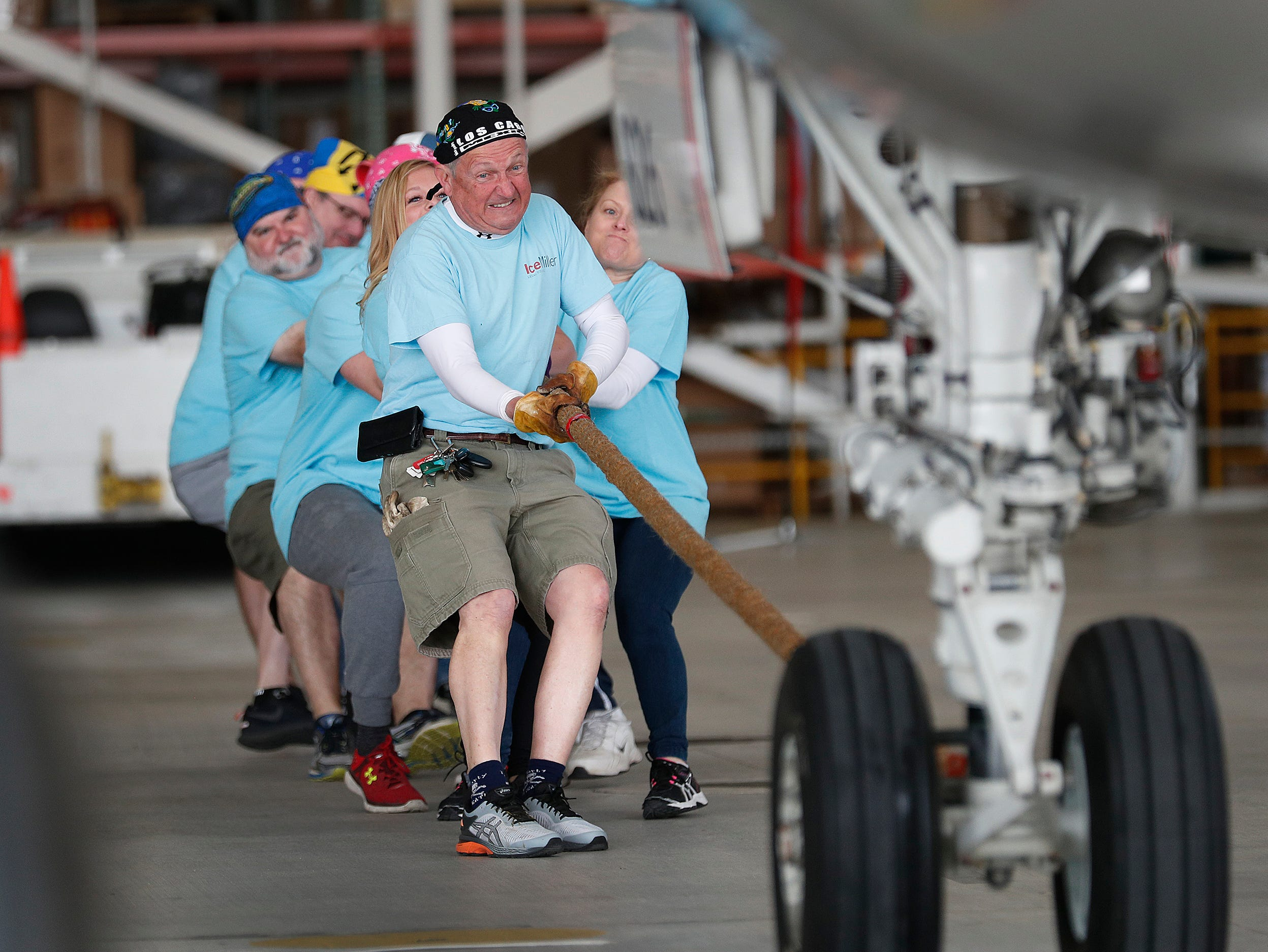 David Carr and his team from Ice Miller take their turn on the rope during the 9th Annual Republic Airways Plane Pull at the Republic Airways Hanger at the Indianapolis International Airport on Saturday, April 13, 2019. The event benefits Indiana Children's Wish Fund, Peyton Manning Children's Hospital, Riley Children's Foundation and A Kid Again. All teams will pull an Embraer 170/175 aircraft 15 feet.