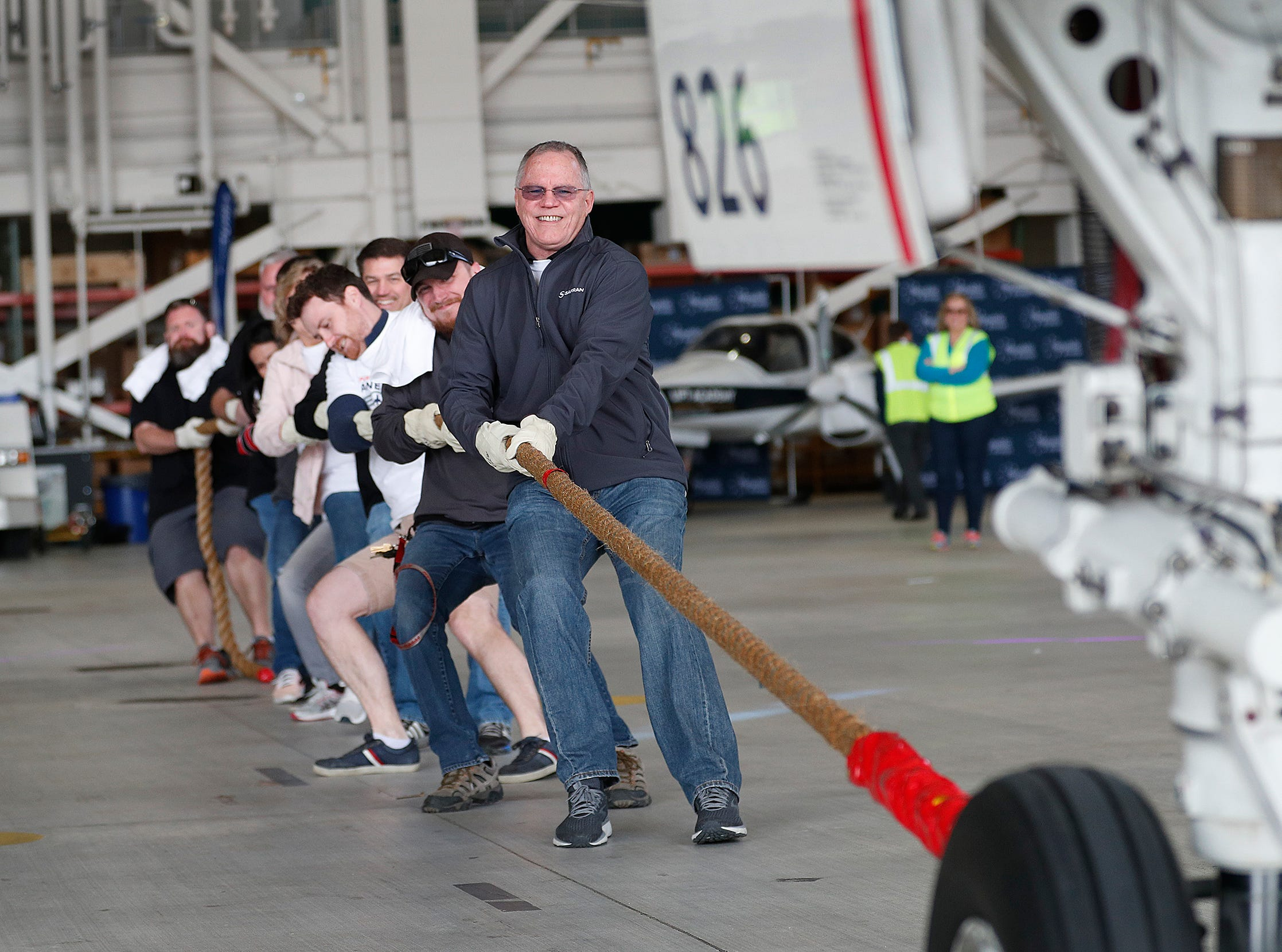 Greg Adkins along with his team from Safran Narcelles Servcies Americas pulls an Embraer 170/175 aircraft 15 feet during the 9th Annual Republic Airways Plane Pull at the Republic Airways Hanger at the Indianapolis International Airport on Saturday, April 13, 2019.