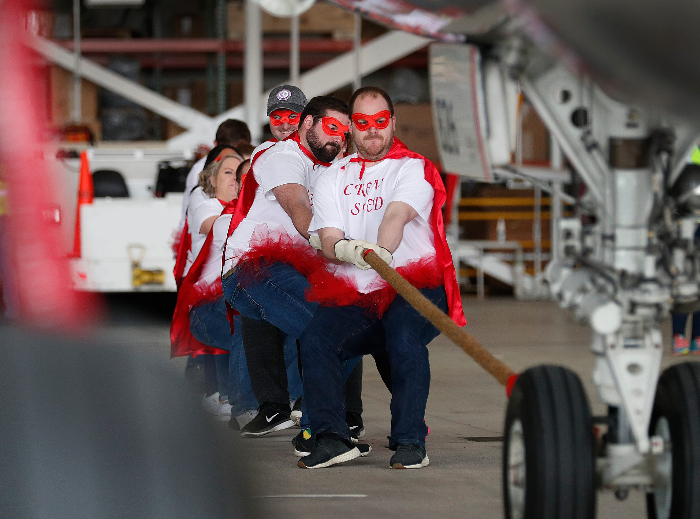Team We'll Pull It for Red Flag Pay (Republic SOC) pulls an Embraer 170/175 aircraft 15 feet during the 9th Annual Republic Airways Plane Pull at the Republic Airways Hanger at the Indianapolis International Airport on Saturday, April 13, 2019.