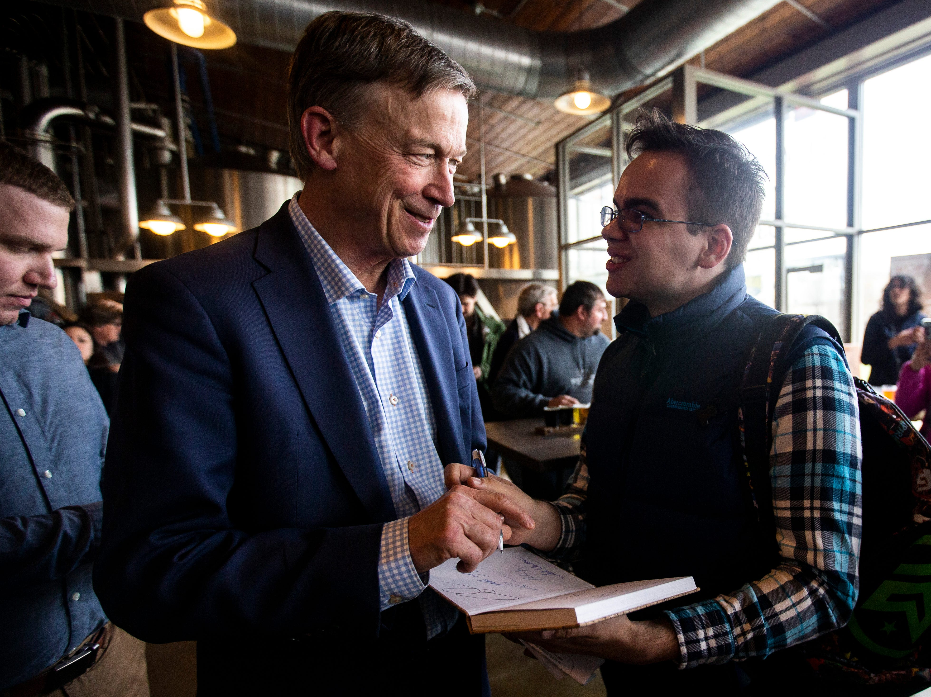 Democratic presidential candidate and former Colorado Gov. John Hickenlooper, left, signs a book for Teagan Roeder of Iowa City during an event on Friday, April 12, 2019, at Backpocket Brewing in Coralville, Iowa.