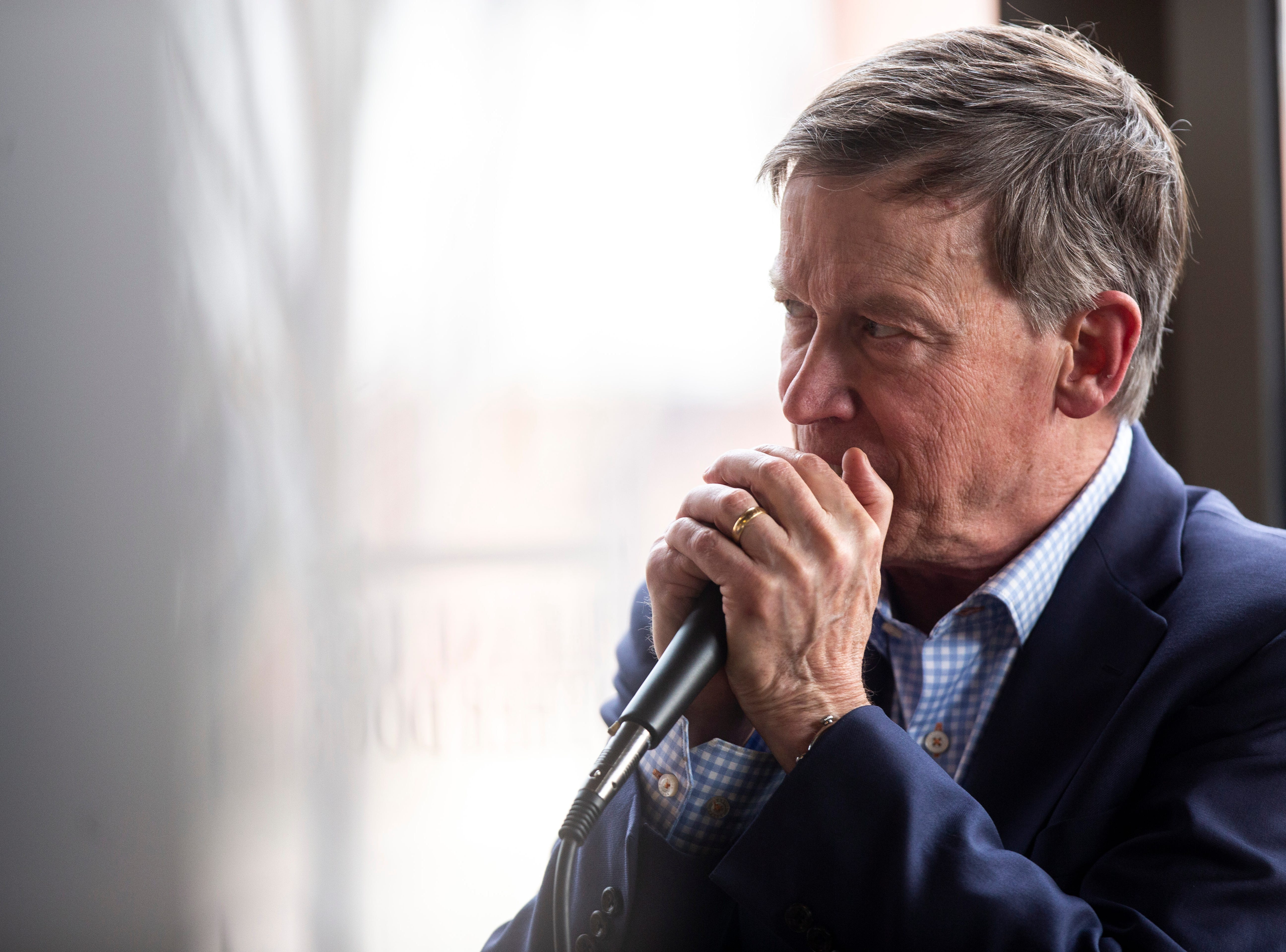 Democratic presidential candidate and former Colorado Gov. John Hickenlooper cups his hands around a microphone while speaking during an event on Friday, April 12, 2019, at Backpocket Brewing in Coralville, Iowa.
