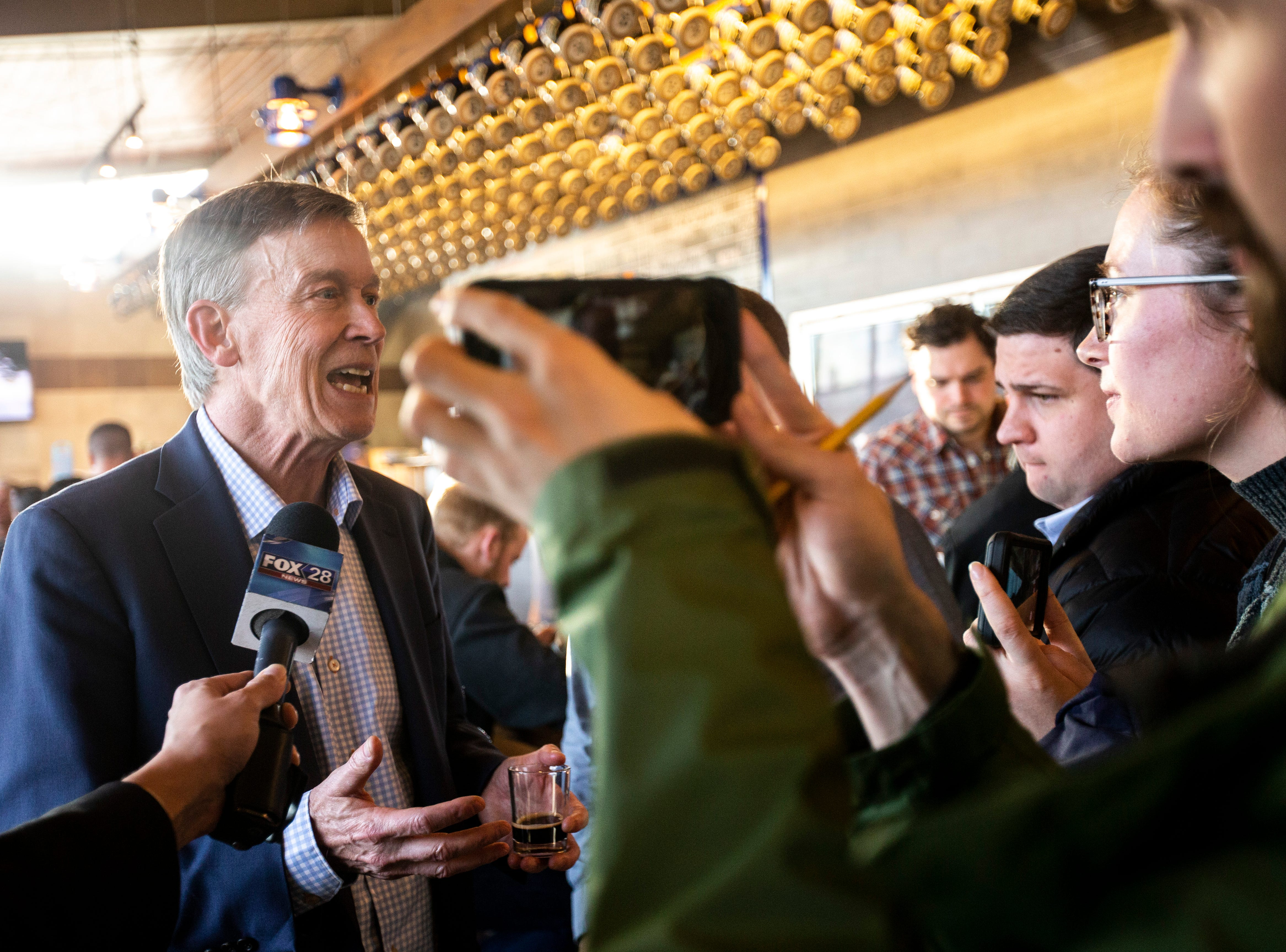 Democratic presidential candidate and former Colorado Gov. John Hickenlooper speaks to reporters after an event on Friday, April 12, 2019, at Backpocket Brewing in Coralville, Iowa.