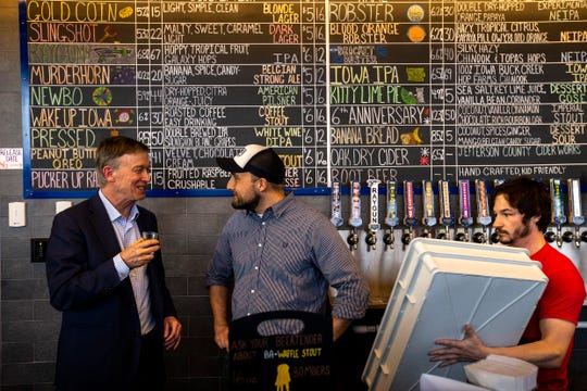 Democratic presidential candidate and former Colorado Gov. John Hickenlooper, left, talks with general manager Andrew Geilenfeld while trying out a peanut butter and Oreo flavored drink during an event on Friday, April 12, 2019, at Backpocket Brewing in Coralville, Iowa. The brewery released the new drink on Friday after brewing about 15 barrels.