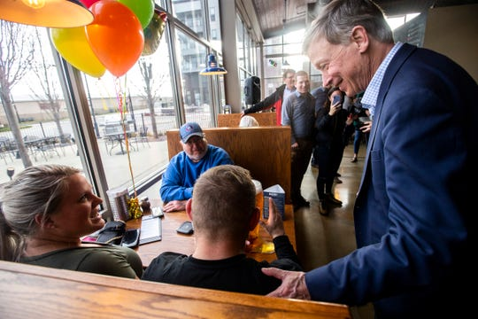 Democratic presidential candidate and former Colorado Gov. John Hickenlooper talks with Keeley, far left, and Chris Arnold with Jim Halvorsen while the three celebrate Keeley Arnold's birthday with a boot of beer during an event on Friday, April 12, 2019, at Backpocket Brewing in Coralville, Iowa.