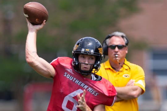 Southern Miss quarterback Tate Whatley loads up to throw as head coach Jay Hopson looks on Saturday, April 13, 2019, during the Black & Gold spring game in Hattiesburg