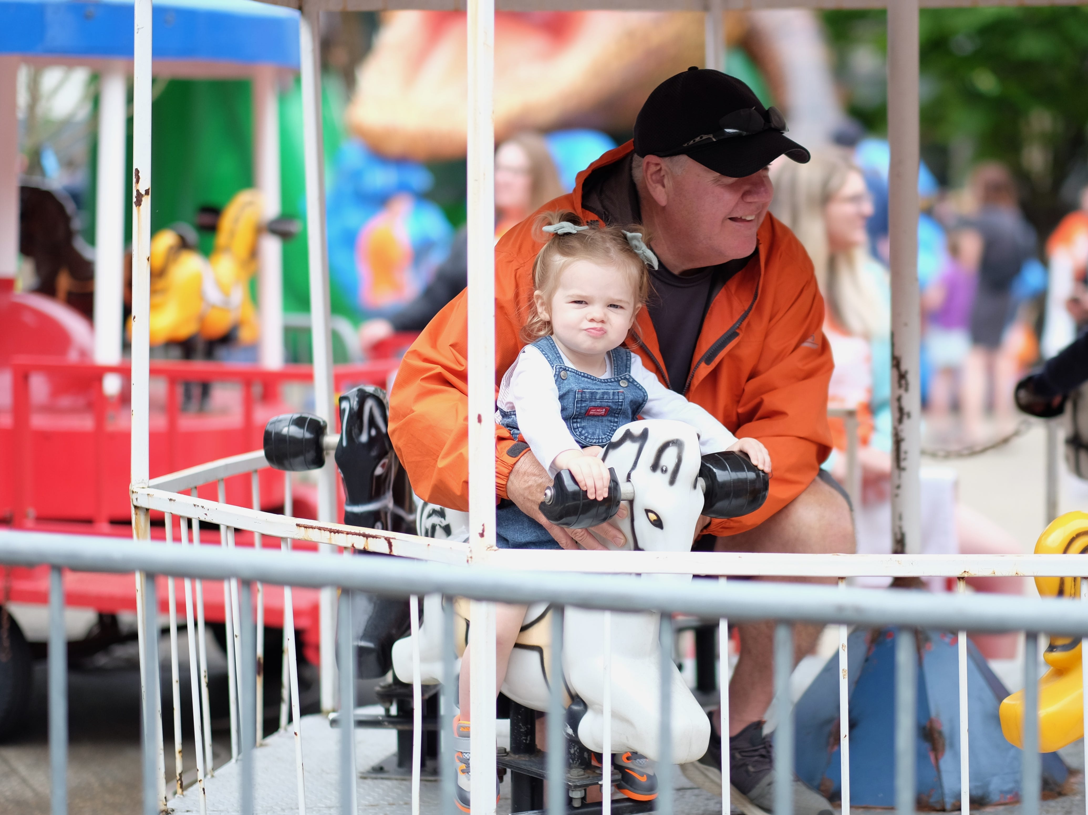Mike Smith rides the carousel with his granddaughter Halli Smith, 1, during the Rossini Festival in Knoxville on Saturday, April 13, 2019. (Shawn Millsaps/Special to News Sentinel)