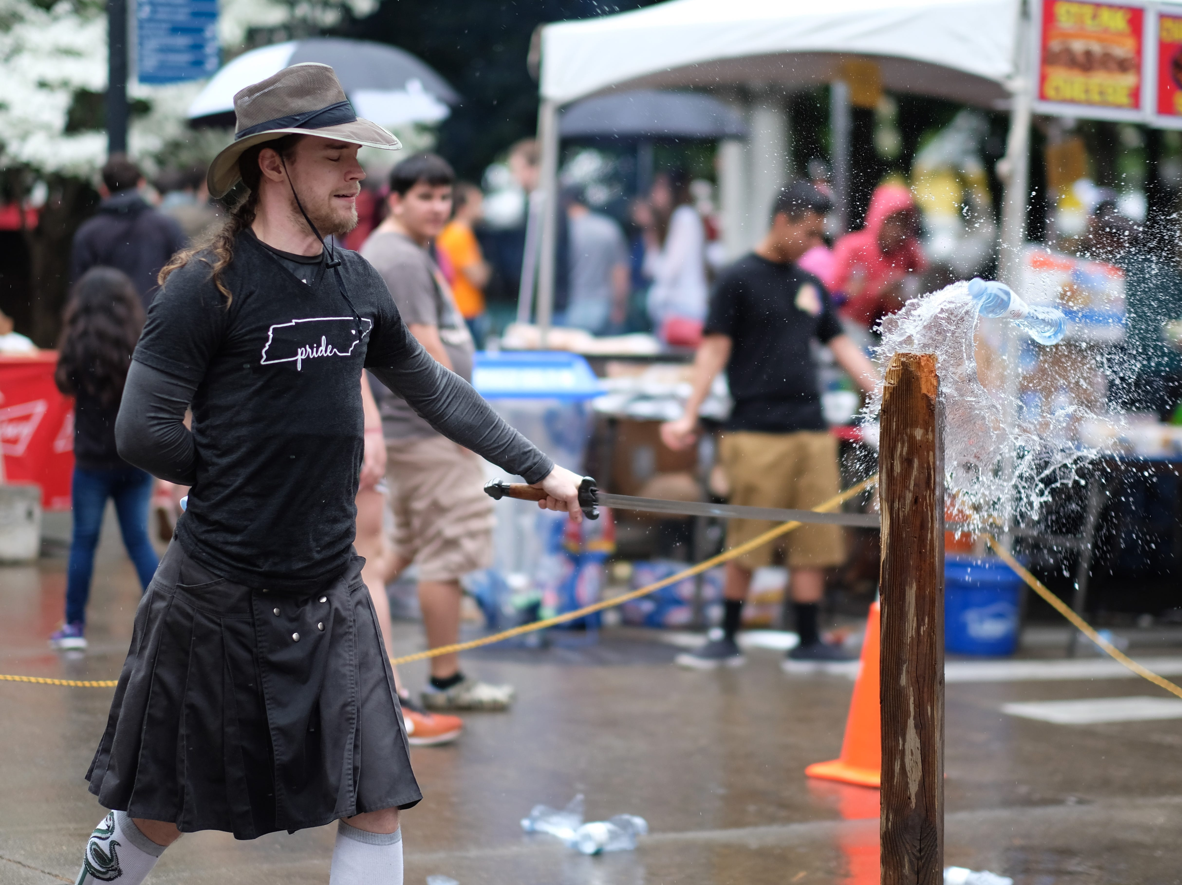 Tom Farmer of Knoxville Academy of the Blade slices a water bottle in half during the Rossini Festival in Knoxville on Saturday, April 13, 2019. (Shawn Millsaps/Special to News Sentinel)