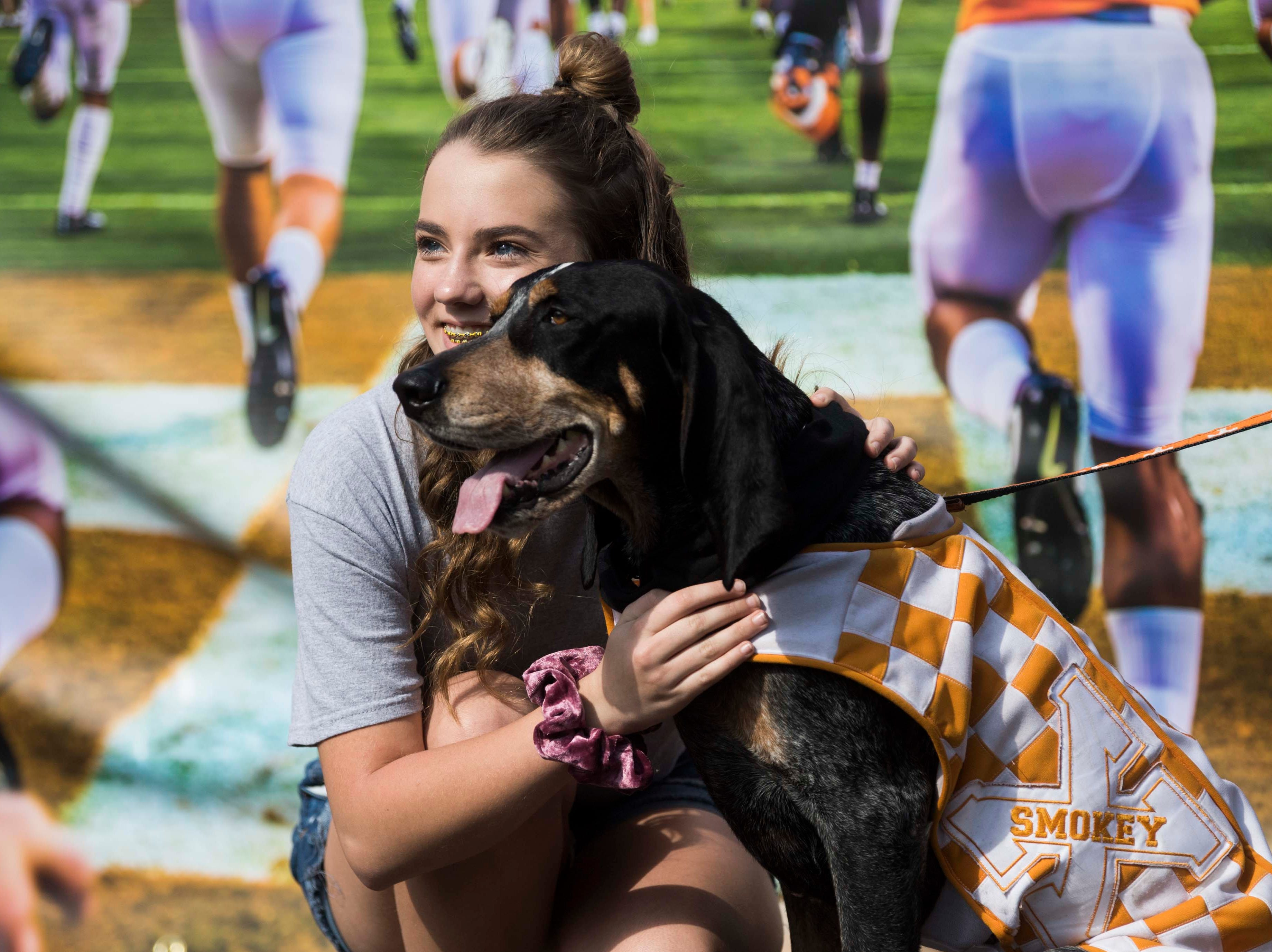 A fan poses with Smokey while waiting for the Vols spring game to begin outside Neyland Stadium in Knoxville Saturday, April 13, 2019.