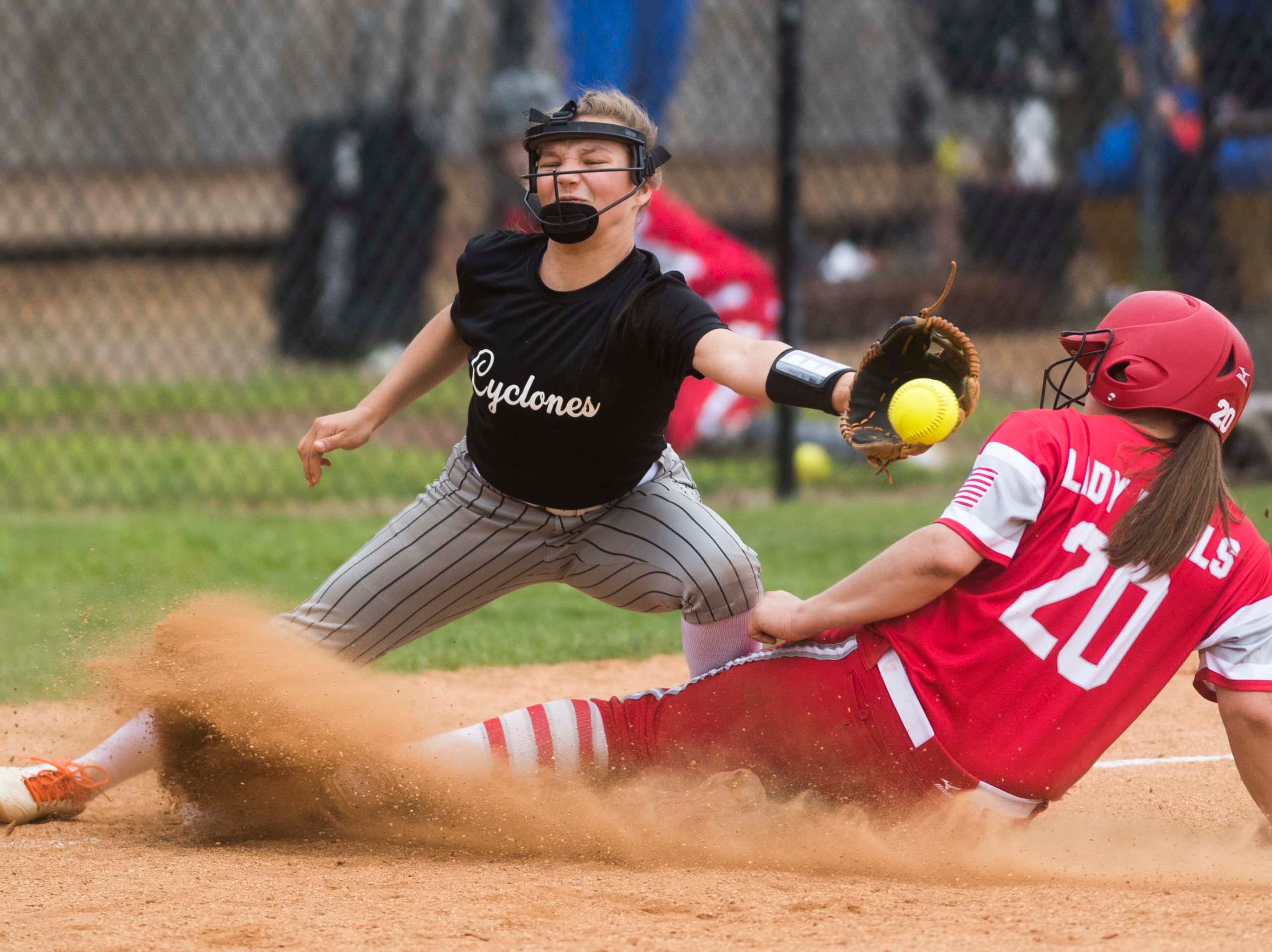 Elizabethton's Maggie Johnson (17) attempts to tag out Halls' (20) during a high school softball game between Halls and Elizabethton at Halls Friday, April 12, 2019. Halls defeated Elizabethton.