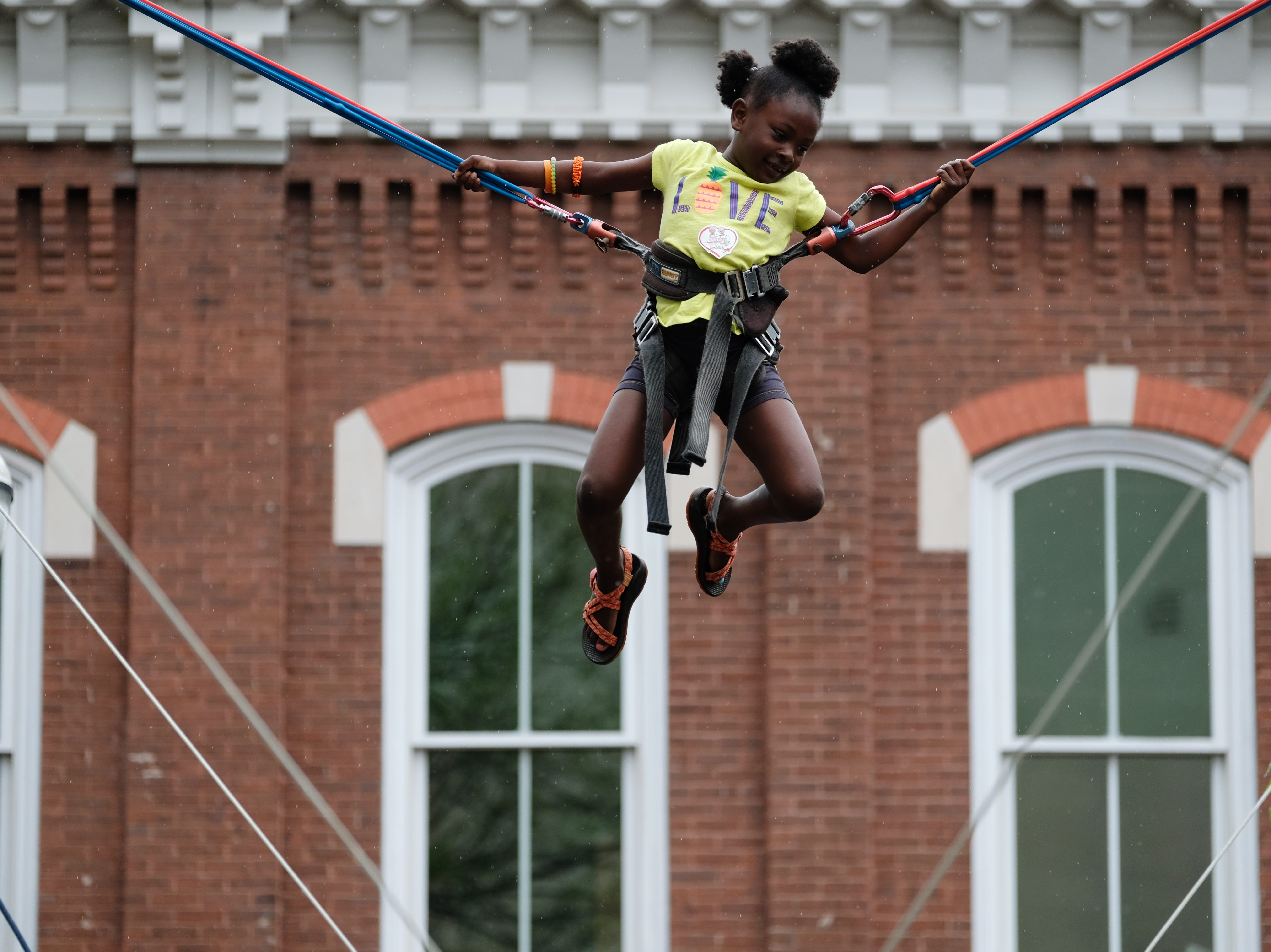 Ra'Ziya Grate, 6, jumps on a trampoline during the Rossini Festival in Knoxville on Saturday, April 13, 2019. (Shawn Millsaps/Special to News Sentinel)