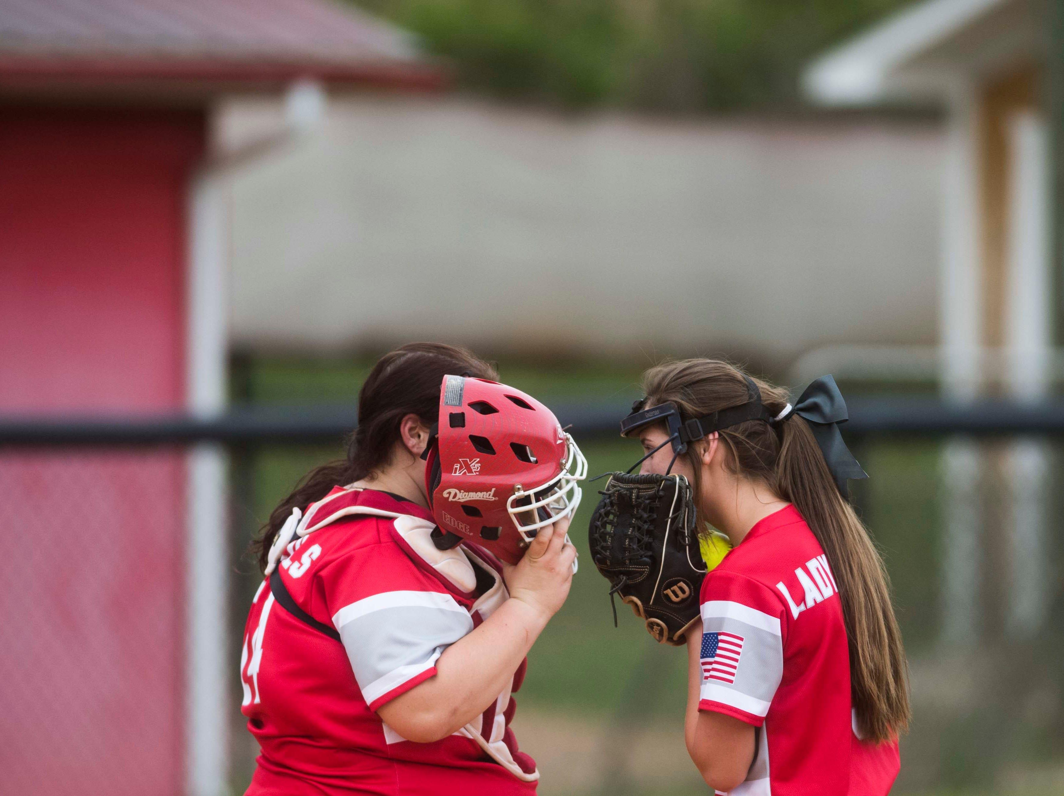 At left Halls' Leyna Gould whispers to Sloane Baldridge (9) during a high school softball game between Halls and Elizabethton at Halls Friday, April 12, 2019. Halls defeated Elizabethton.