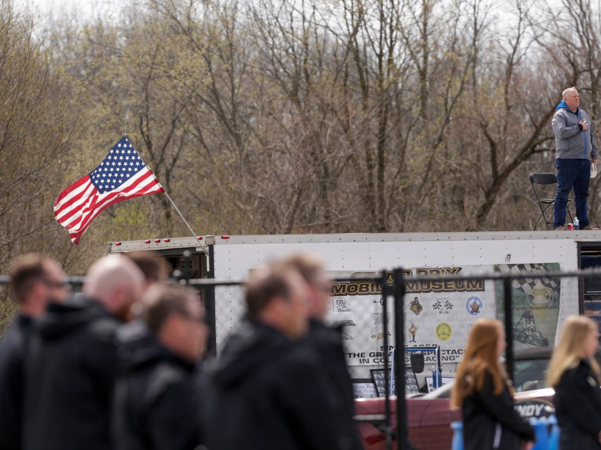A man stands on a trailer during the playing of the national anthem during the 62nd Grand Prix, Saturday, April 13, 2019, in West Lafayette.