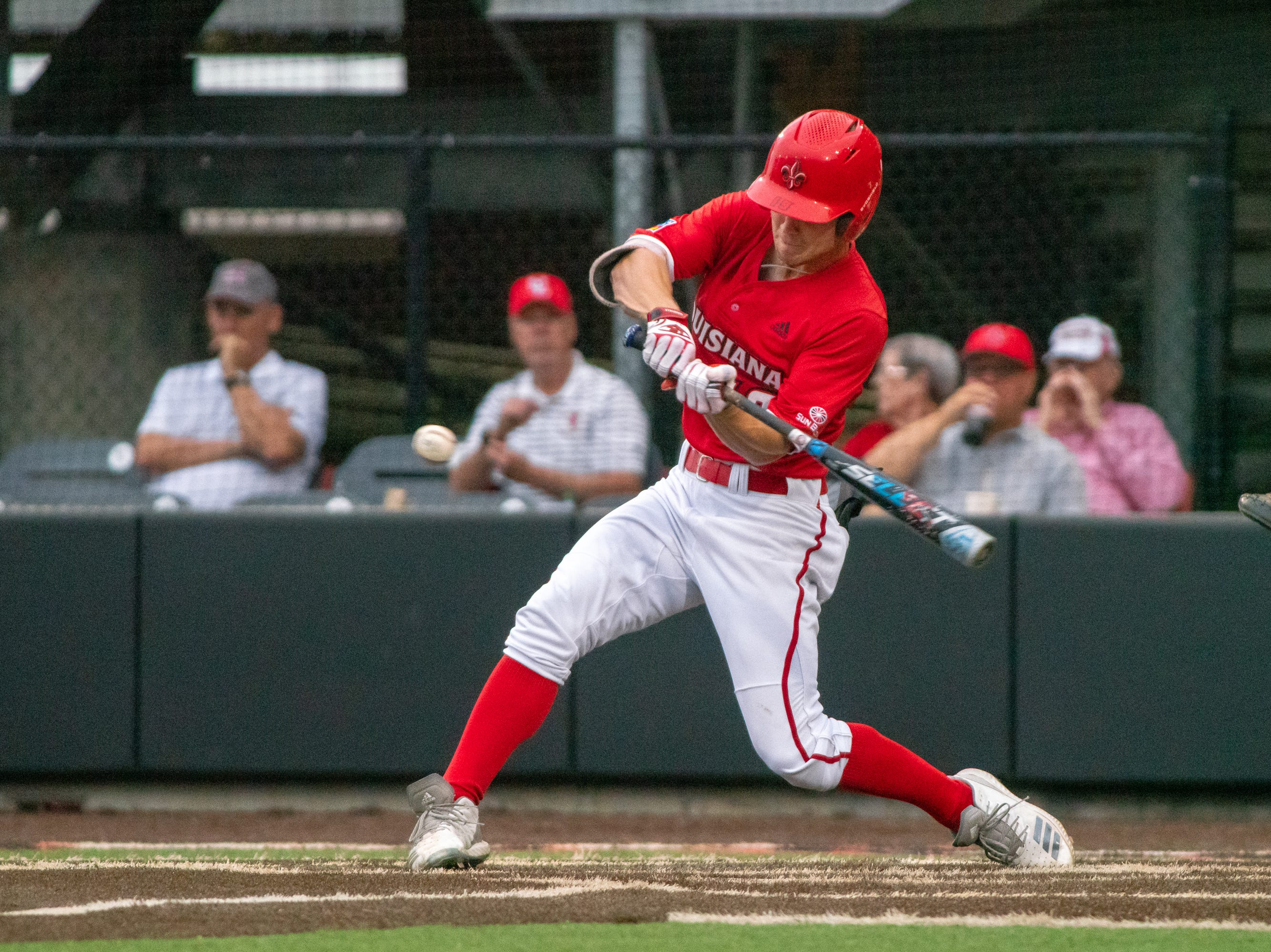 """UL's Hunter Kasuls swings at the incoming pitch as the Ragin' Cajuns take on the South Alabama Jaguars at M.L. """"Tigue"""" Moore Field on Friday, April 4, 2019."""