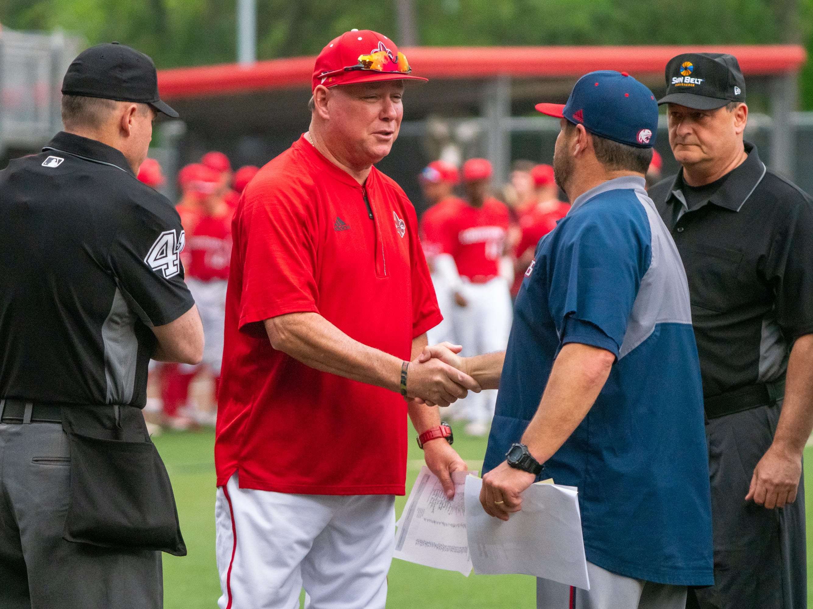 """UL's head coach Tony Robichaux meets with South Alabama's head coach Mark Calvi at home plate before the game as the Ragin' Cajuns take on the South Alabama Jaguars at M.L. """"Tigue"""" Moore Field on Friday, April 4, 2019."""