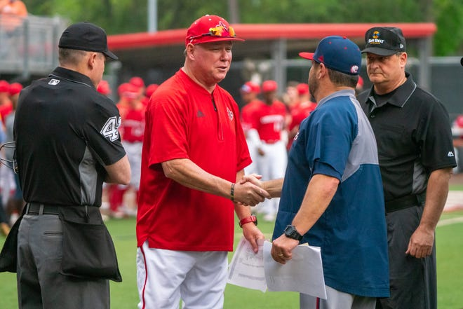 """UL's head coach Tony Robichaux meets with South Alabama's head coach Mark Calvi at home plate before the game as the Ragin' Cajuns take on the South Alabama Jaguars at M.L. """"Tigue"""" Moore Field April 4, 2019."""