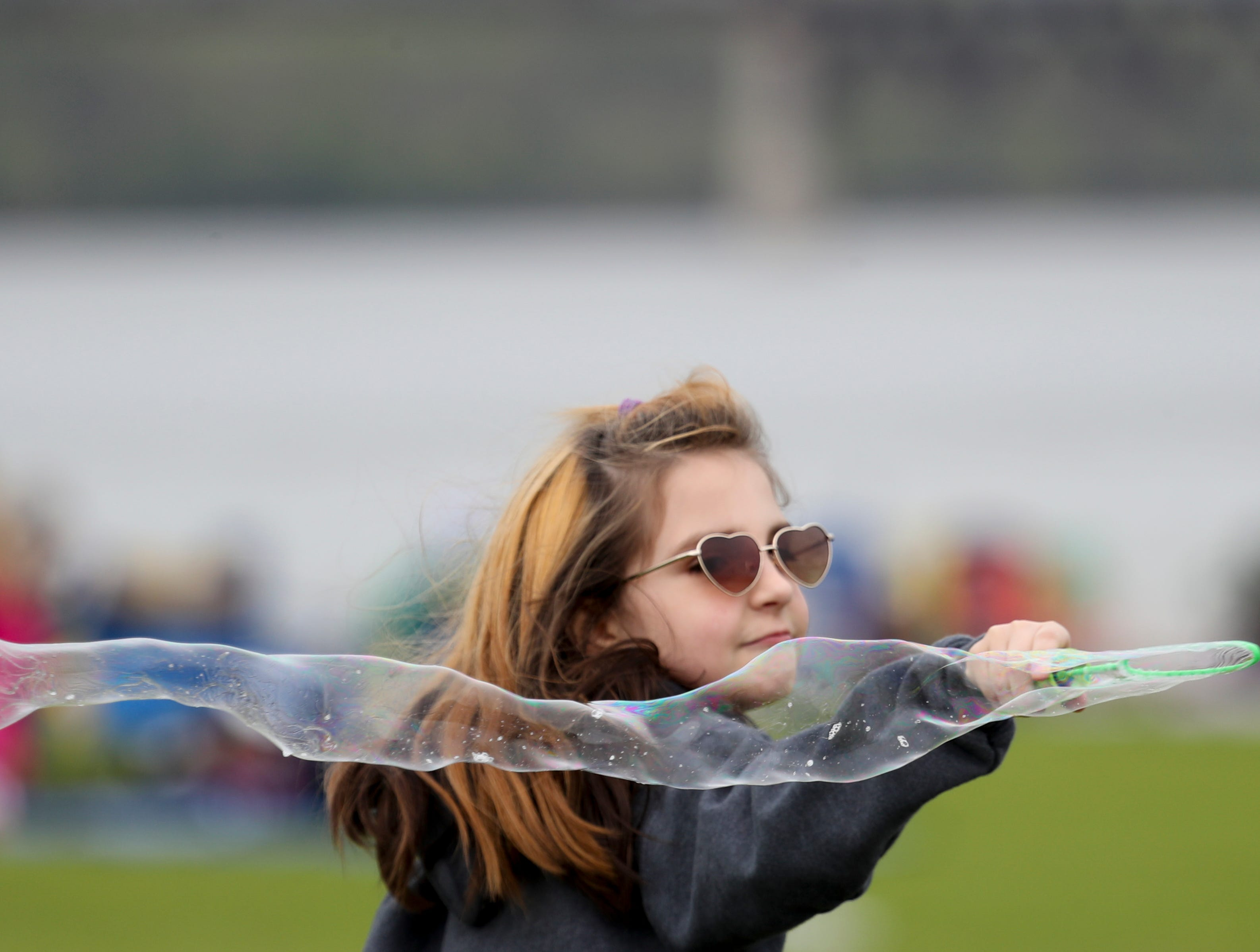 Trinity Rolfe enjoys her bubble maker at Thunder Over Louisville airshow to being on April 13.