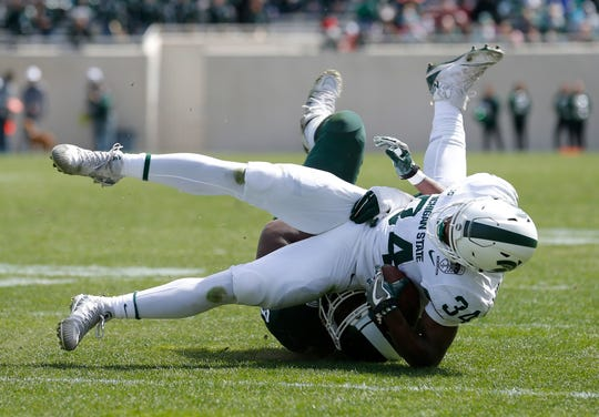 Michigan State freshman running back Anthony Williams (34) is tackled by Naquan Jones during their spring NCAA college football scrimmage, Saturday, April 13, 2019, in East Lansing, Mich. (AP Photo/Al Goldis)