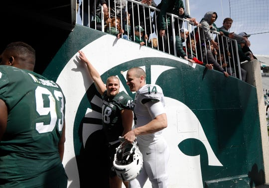 Michigan State quarterback Brian Lewerke, right, and defensive end Kenny Willekes (48) leave the field after their spring NCAA college football scrimmage, Saturday, April 13, 2019, in East Lansing, Mich. (AP Photo/Al Goldis)