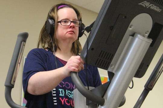Makisha Ralph, 31, does a workout on an elliptical machine at the Marion Family YMCA on Thursday. Since suffering a near-fatal blood clot in 2017, she has lost 100 pounds.
