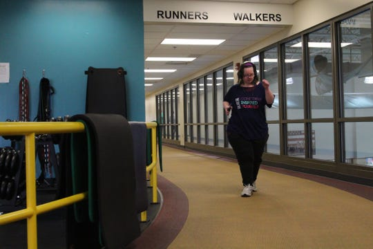 Makisha Ralph, 31, makes her way around a track at the Marion Family YMCA on Thursday. Since suffering a near-fatal blood clot in 2017, she has lost 100 pounds.