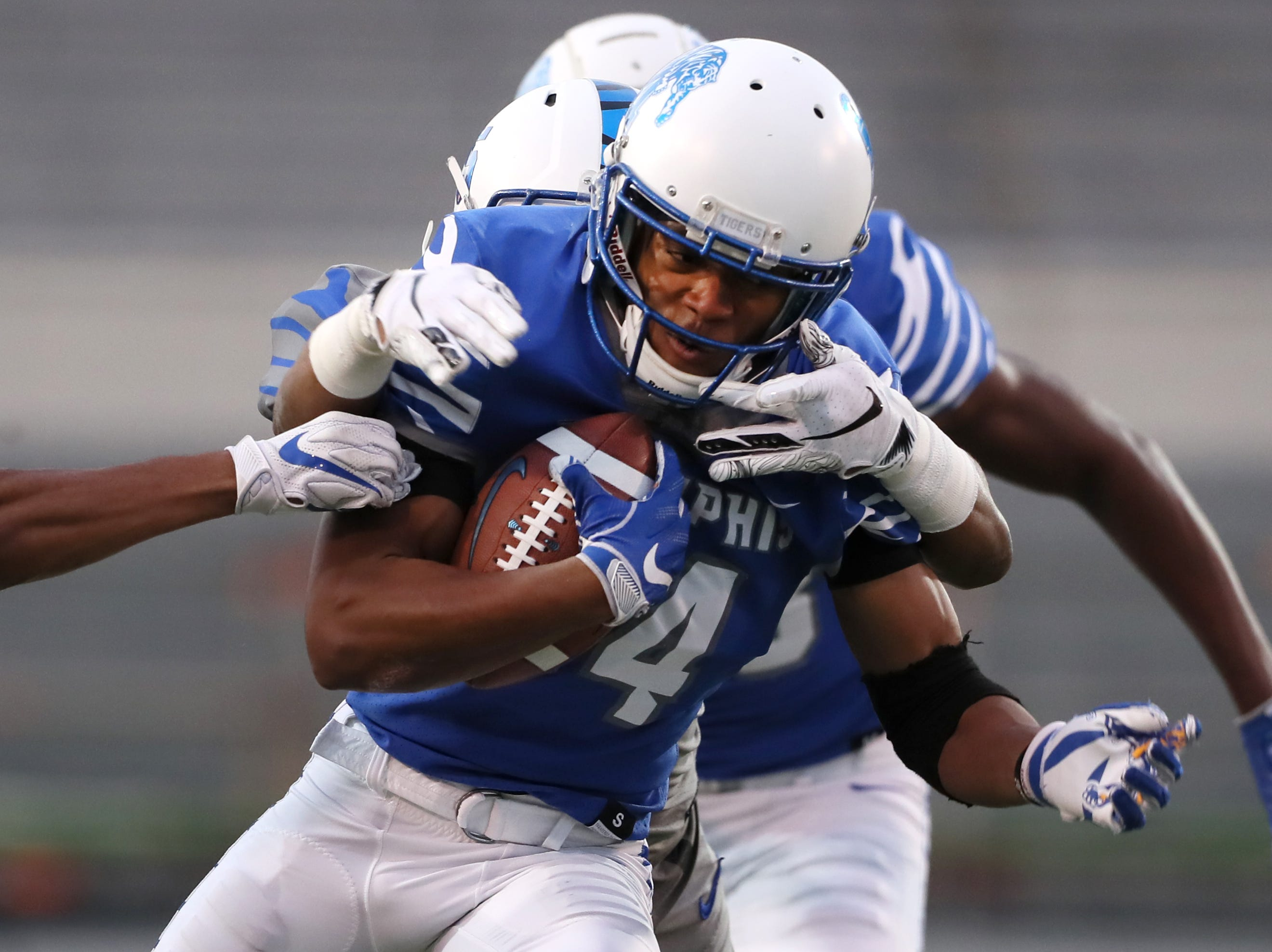Memphis Tigers wide receiver Antonio Gibson breaks downfield as defenders hang on during their Friday Night Stripes spring game at Liberty Bowl Memorial Stadium on Friday, April 12, 2019.