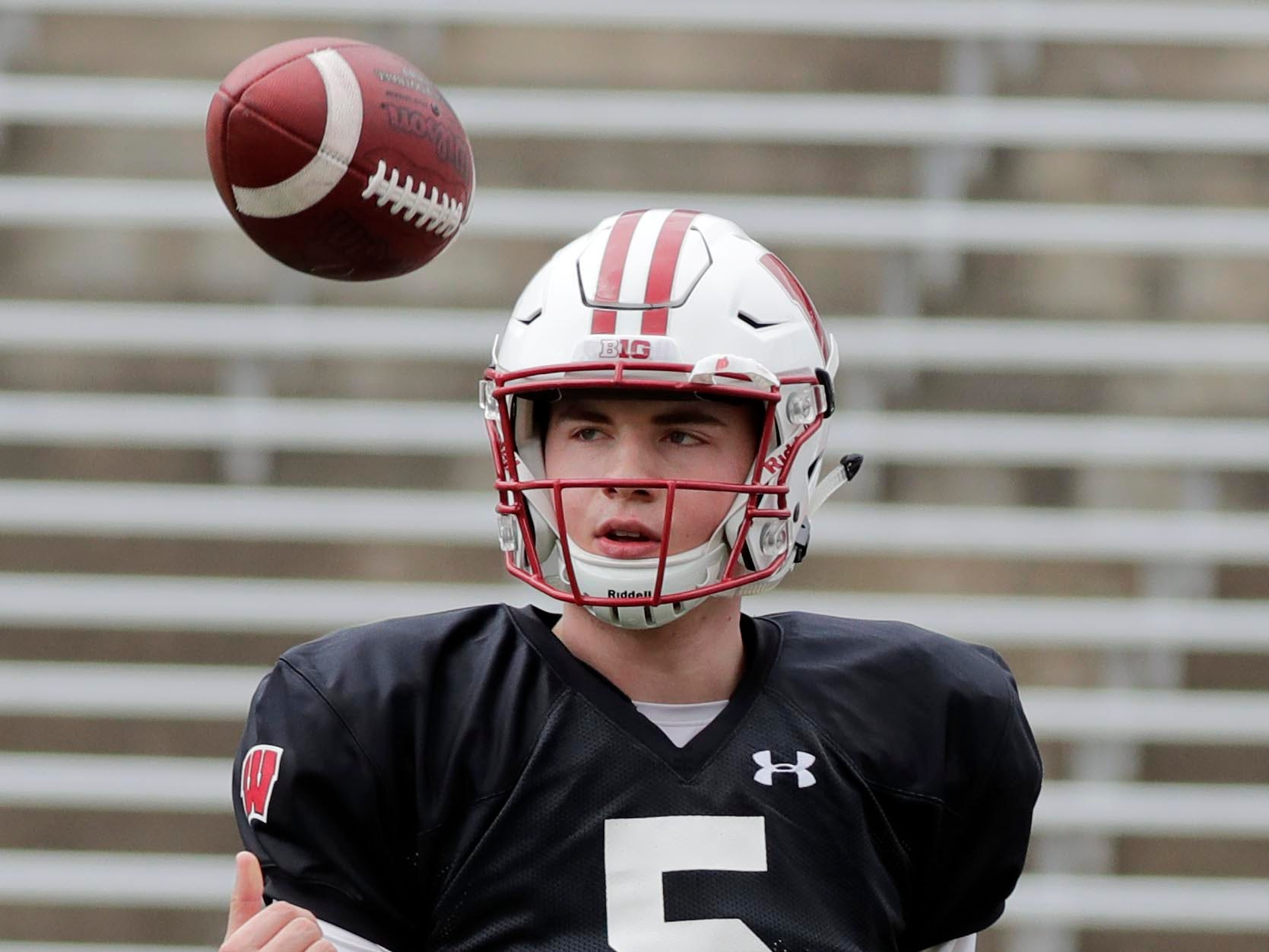 Freshman quarterback Graham Mertz flips the football around during practice Saturday.