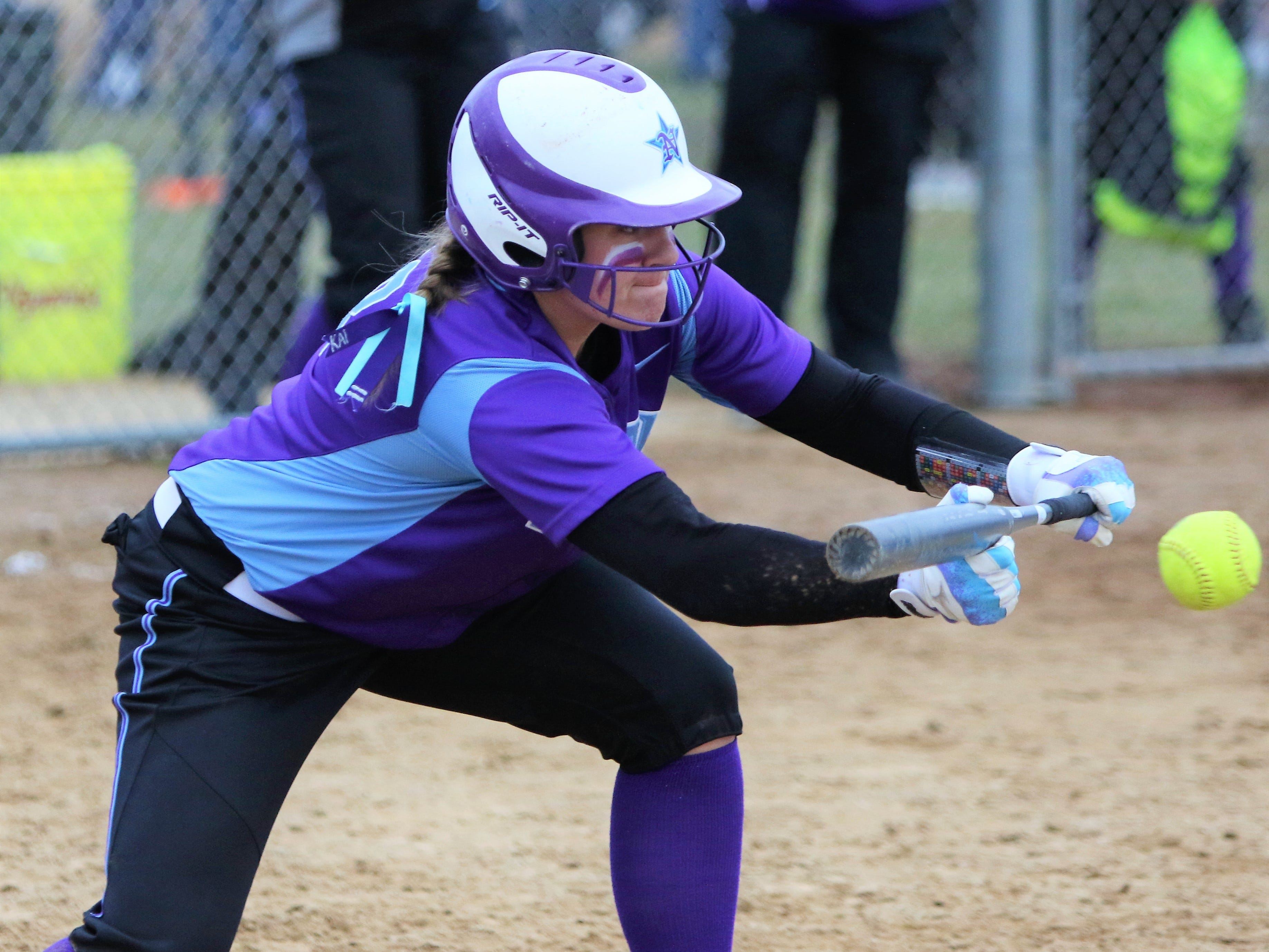 Waukesha North senior Maddy Anderson gets a bunt down to score a run against Muskego on April 12, 2019.