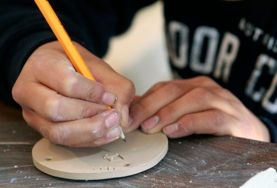 Joe McCrea, 12, works on a tile that will be part of an upcoming are installation.