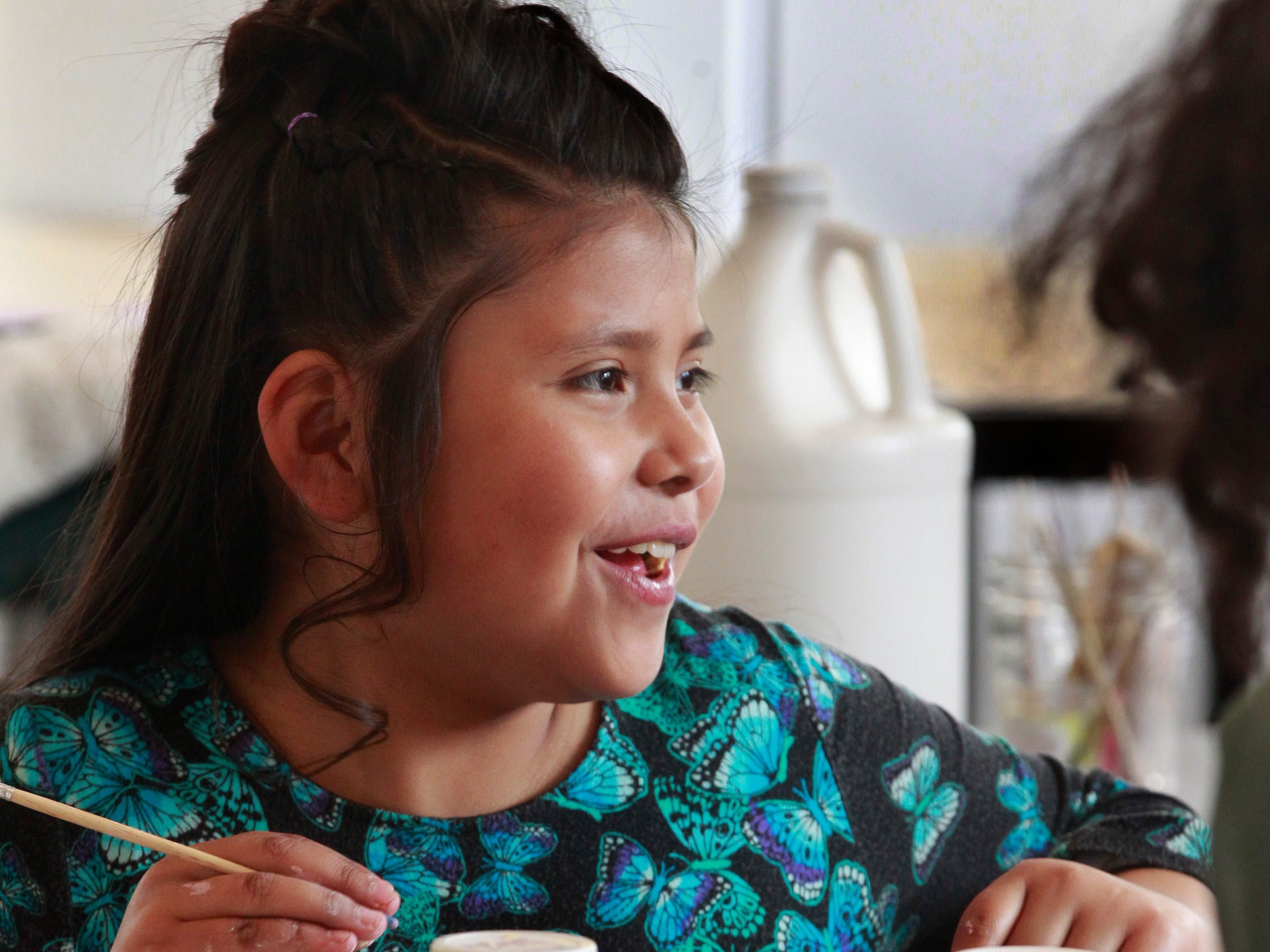 Yazmin Dominguez, 9, is all smiles while working on a tile at the 26th Street Project for an upcoming art installation.  Lori Gramling started the art program to engage young children in ceramic arts.