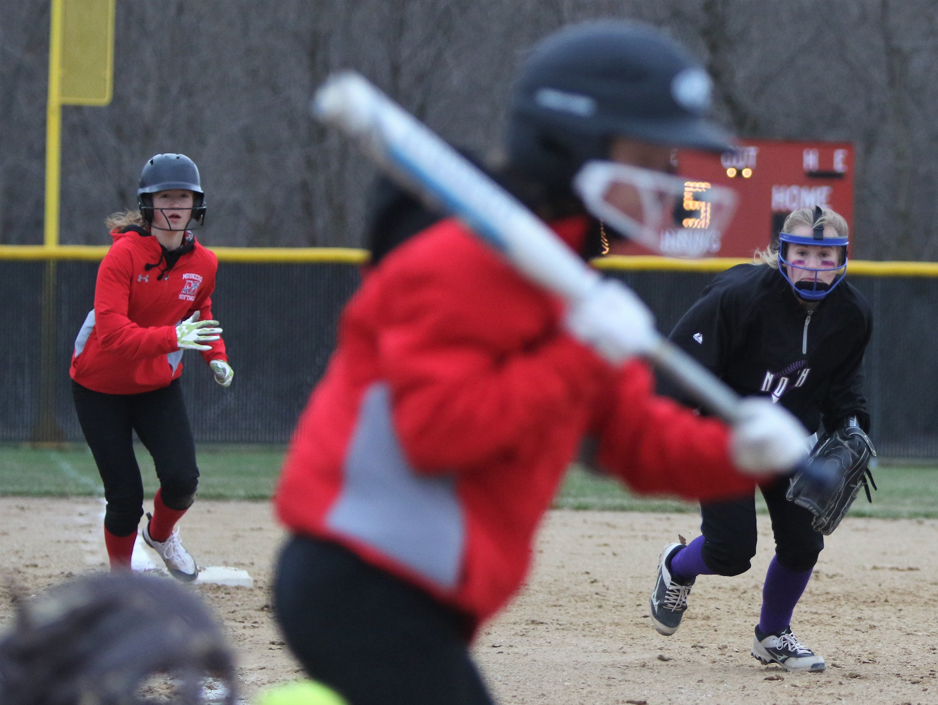 Players from Muskego and Waukesha North creep toward home plate as a pitch crosses for a strike during a game on April 12, 2019.