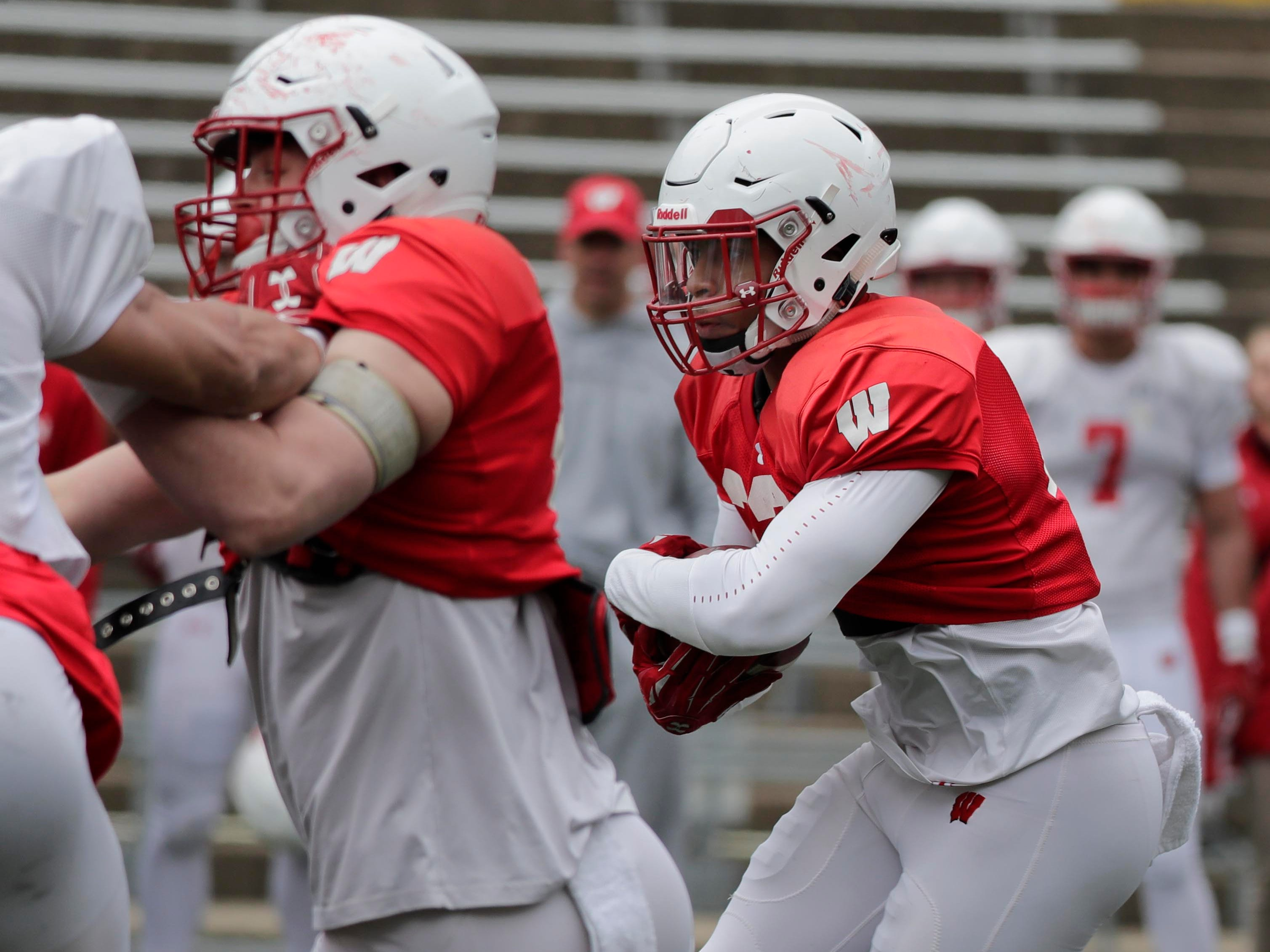 Badgers running back Jonathan Taylor looks for an opening during practice.