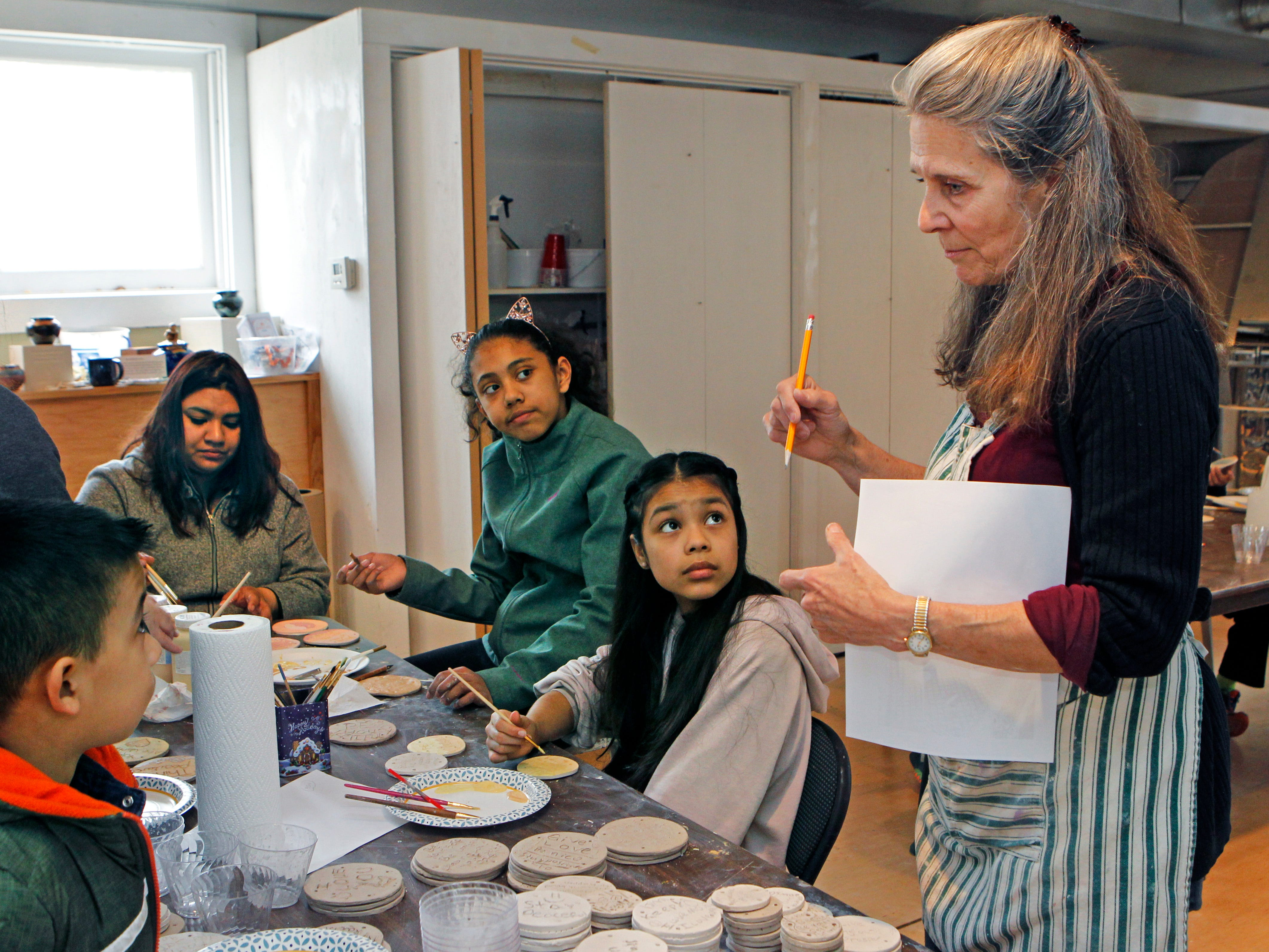 Lori Gramling gives some pointers to youths who are painting their tiles.