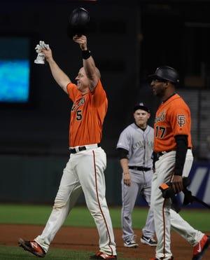 San Francisco Giants' Erik Kratz (5) celebrates at the end of an 18 inning baseball game against the Colorado Rockies Saturday in San Francisco.