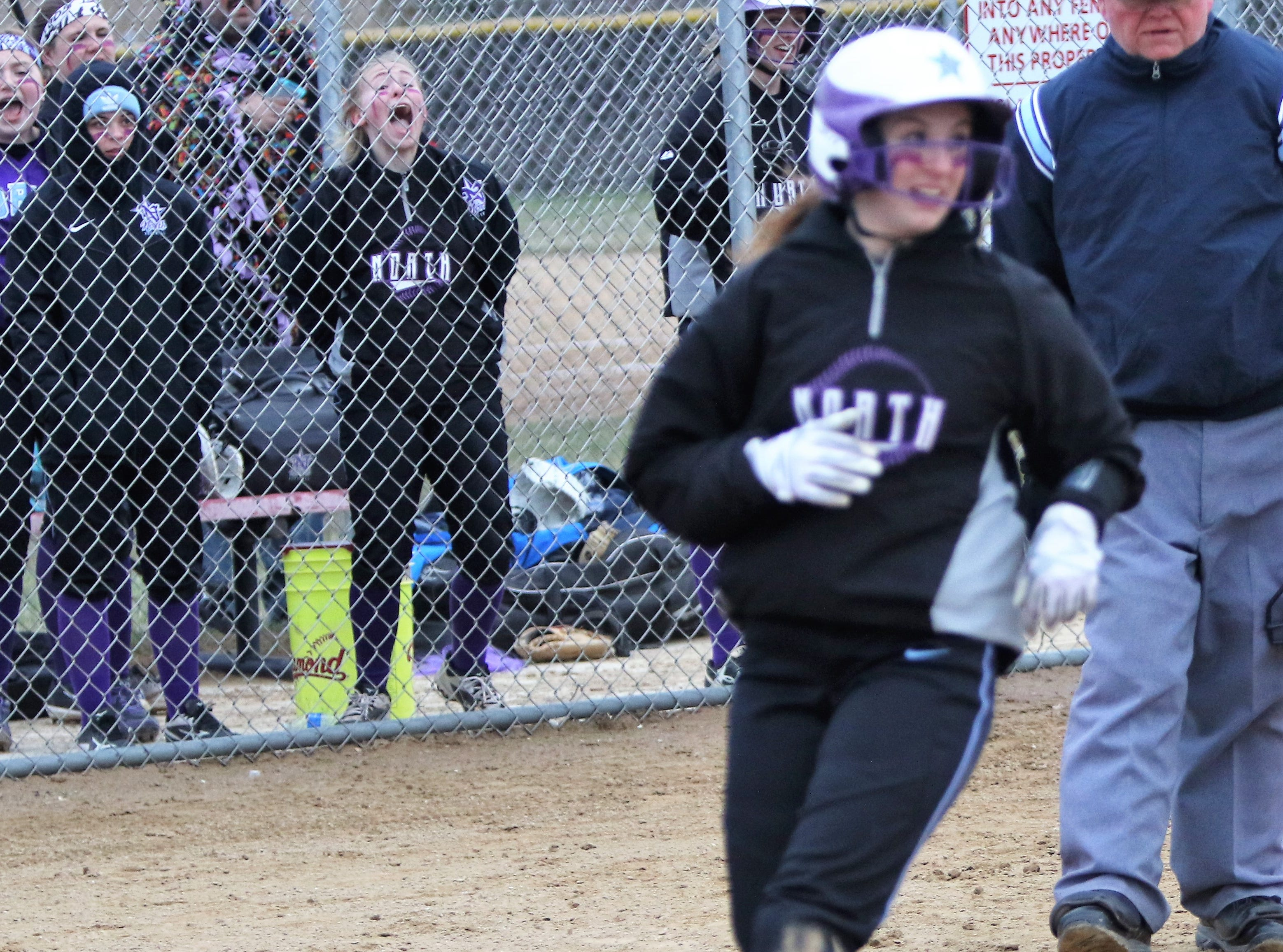 Waukesha North teammates react as teammate Jenny Gibbs scores a run against Muskego on April 12, 2019.