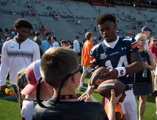 Auburn quarterback Malik Willis (14) signs autographs during the A-Day spring practice gameat Jordan-Hare Stadium in Auburn, Ala., on Saturday, April 13, 2019.
