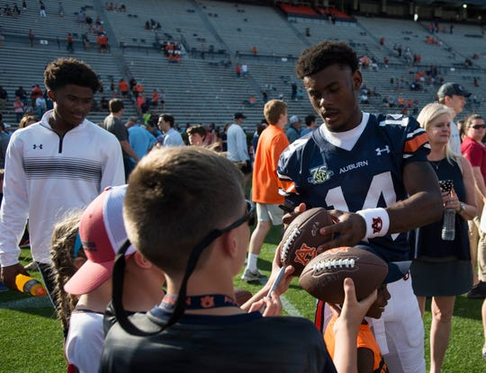 Auburn quarterback Malik Willis (14) signs autographs during the A-Day spring practice gameat Jordan-Hare Stadium in Auburn, Ala., on Saturday, April 13, 2019.