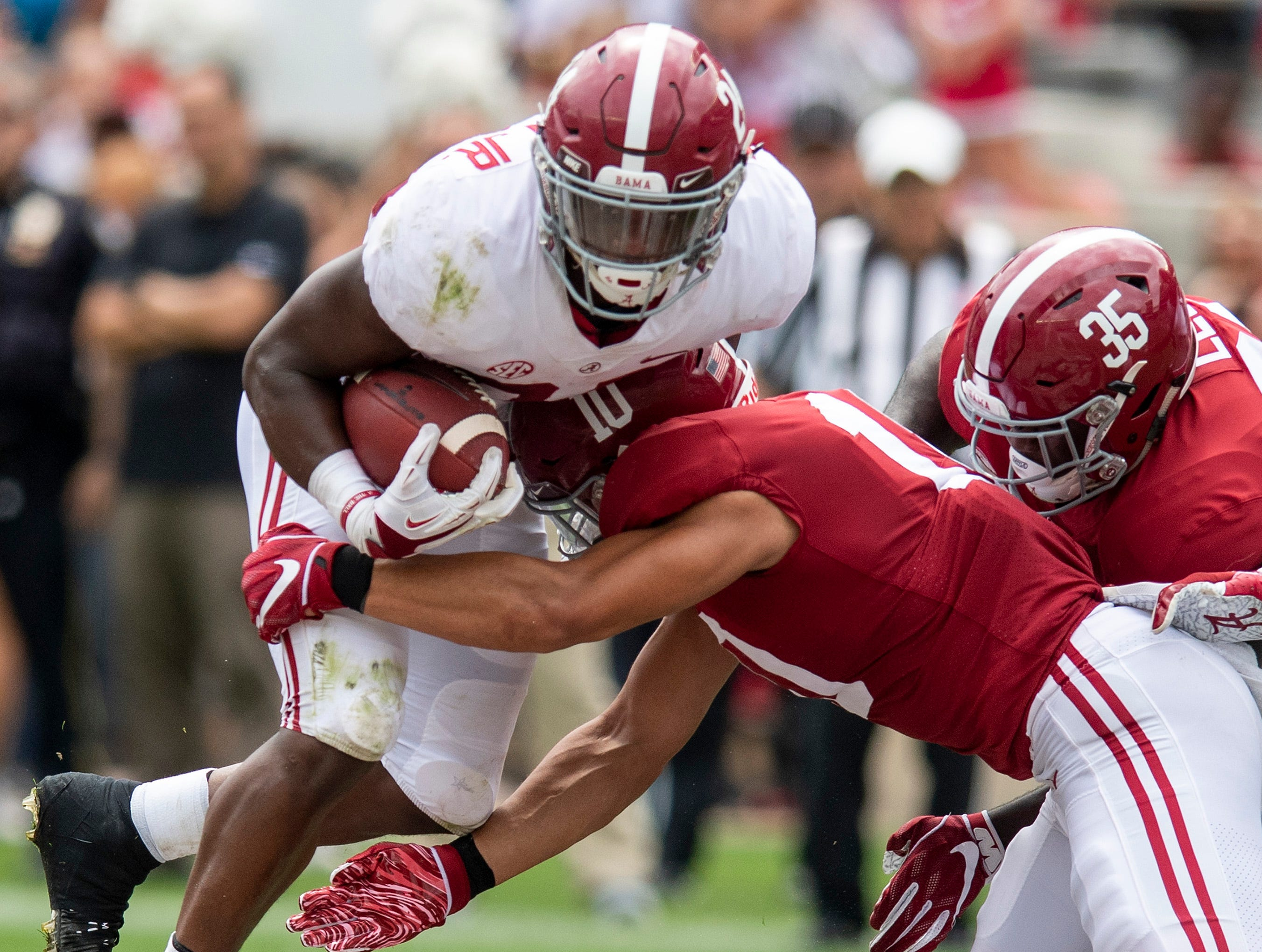 Running back Brian Robinson, Jr., (24) is hit by 