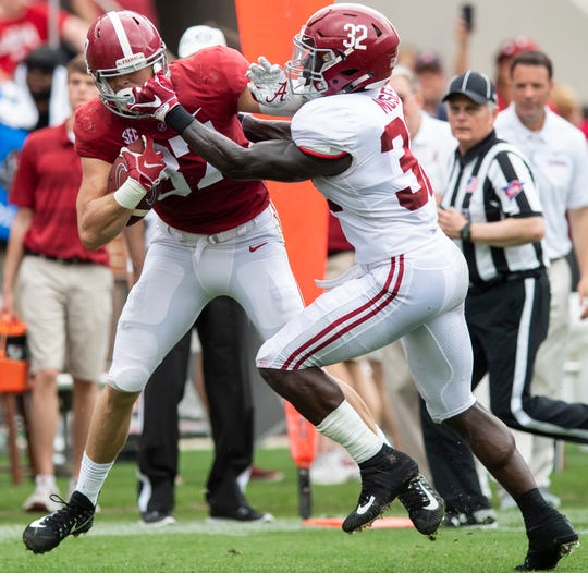 Linebacker Dylan Moses (32) gets in the facemark of tight end Miller Forristall (87) during first half action in the Alabama A-Day spring football scrimmage game at Bryant Denny Stadium in Tuscaloosa, Ala., on Saturday April 13, 2019.