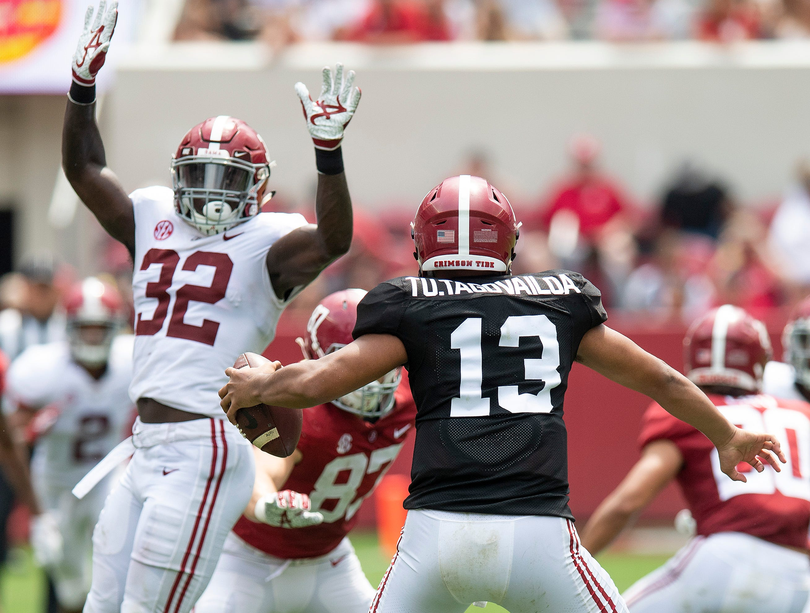 Quarterback Tua Tagovailoa (13) puts a move on linebacker Dylan Moses (32) during first half action in the Alabama A-Day spring football scrimmage game at Bryant Denny Stadium in Tuscaloosa, Ala., on Saturday April 13, 2019.