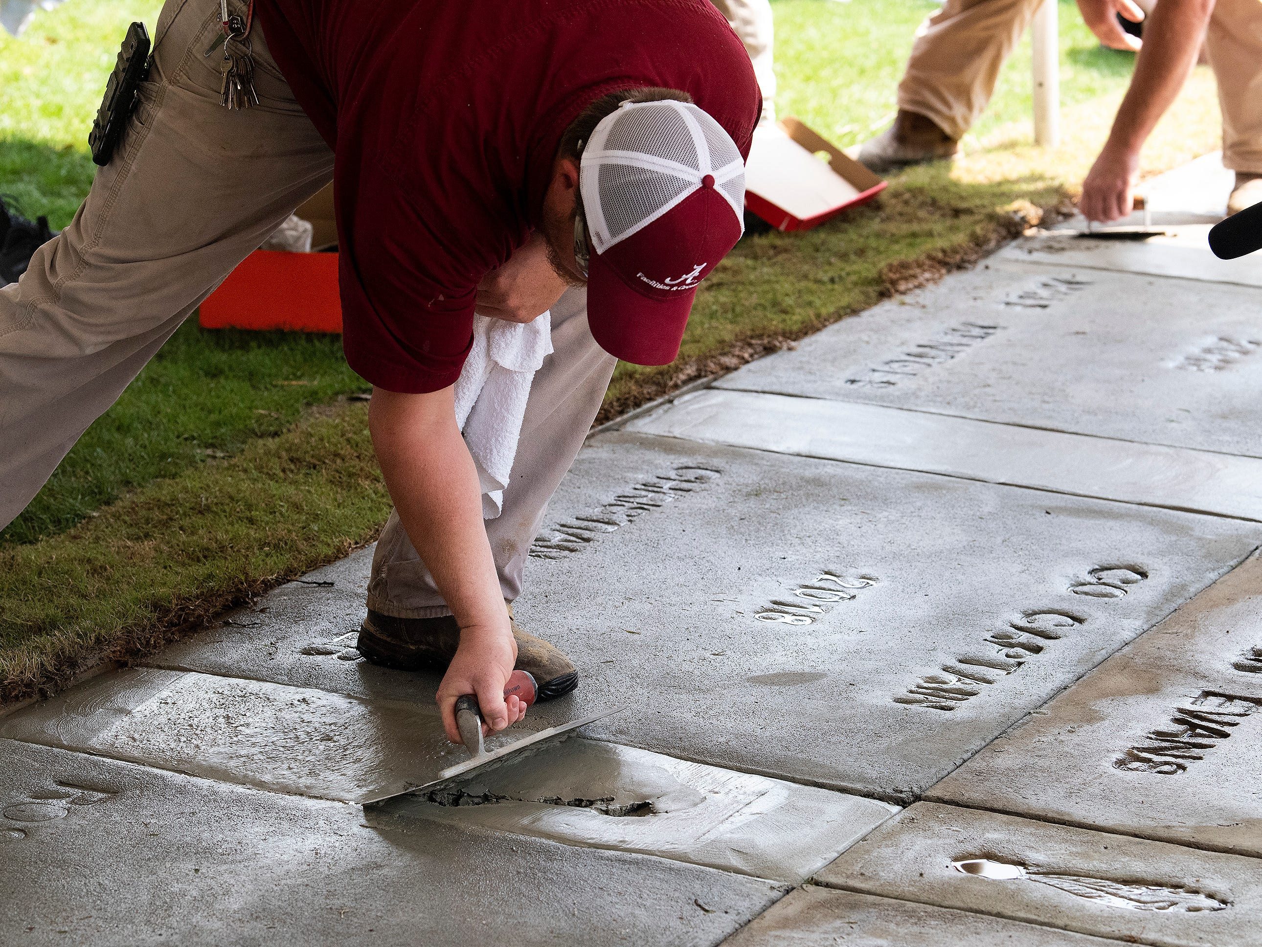 A worker repairs the accidental footprint made by Christian Miller during the Alabama football team captain ceremony at Denny Chimes on the Alabama campus in Tuscaloosa, Ala., on Saturday April 13, 2019.