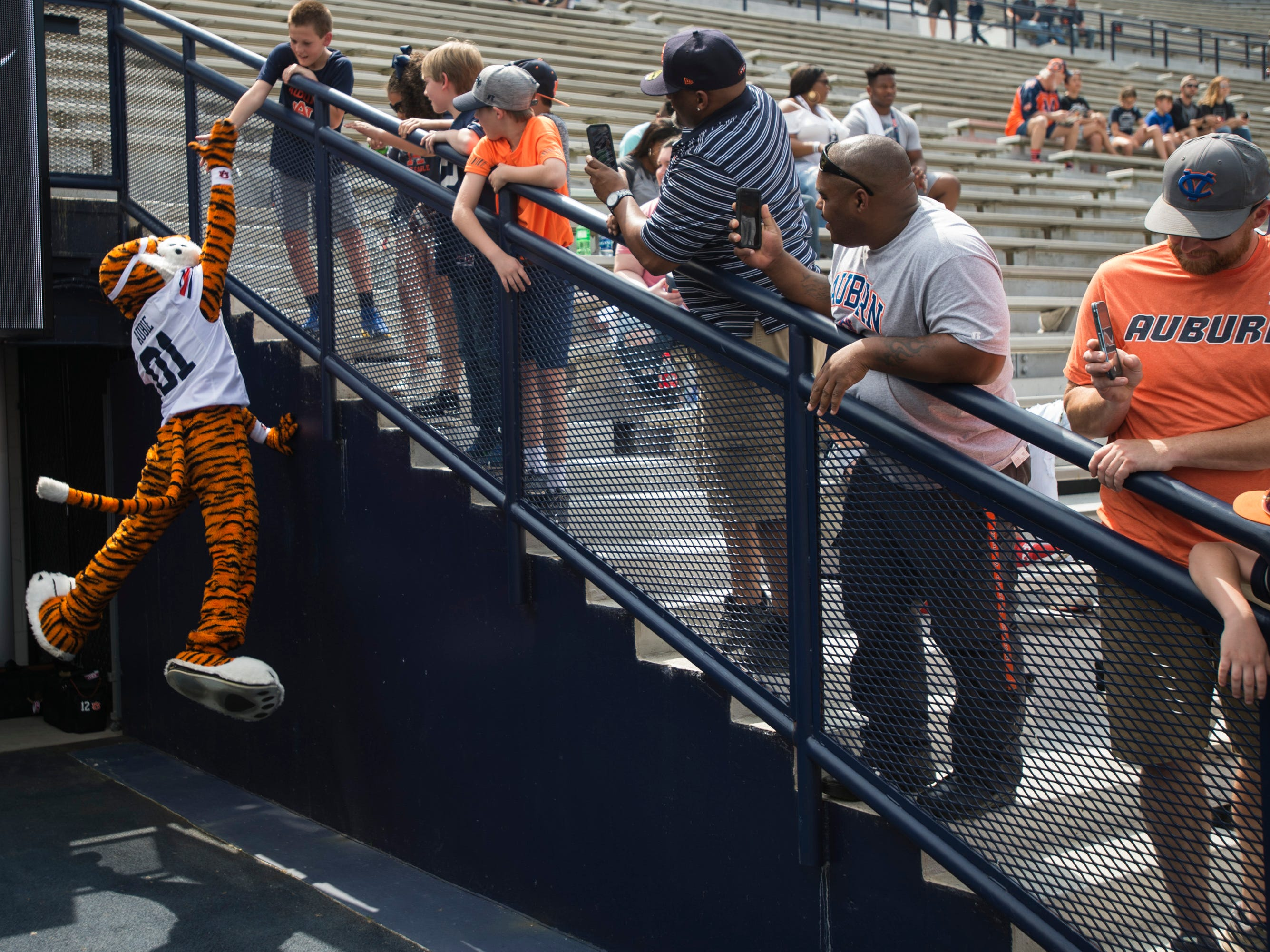 Auburn mascot, Aubie, high fives a fan during the A-Day spring practice gameat Jordan-Hare Stadium in Auburn, Ala., on Saturday, April 13, 2019.