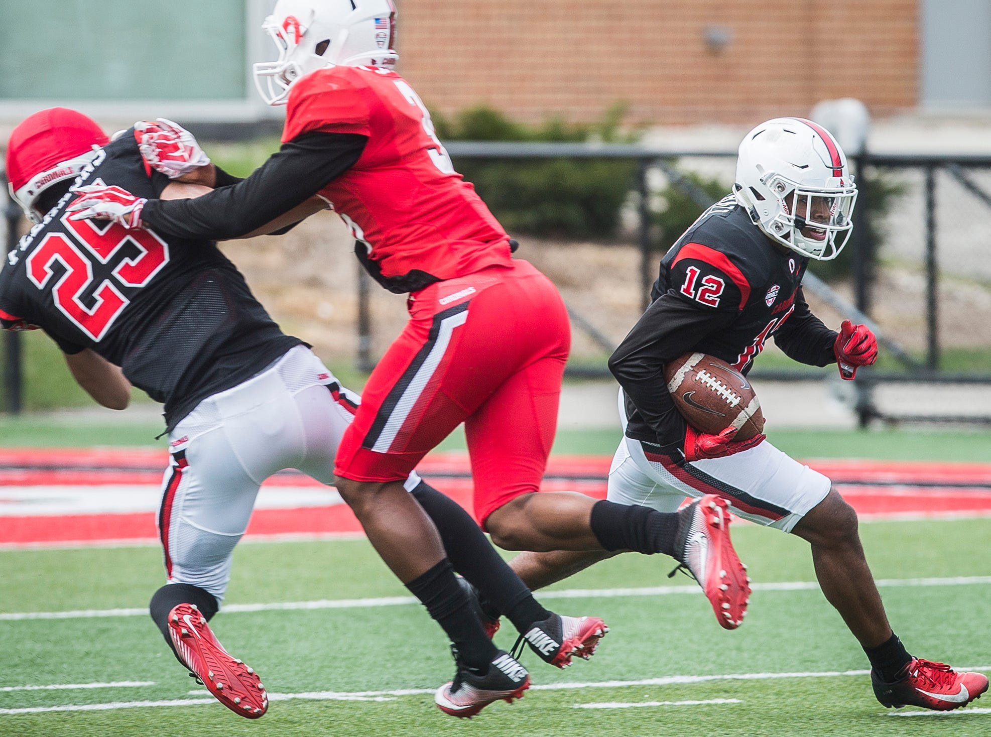Ball State's Justin Hall slips past defenders during the team's Spring Game at Scheumann Stadium Saturday, April 13, 2019.