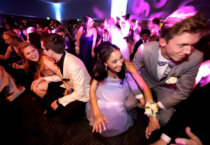 Simone Llorens, left and Connor Anderson get low during a line dance song at Blackman's prom on Friday April 12, 2019, at MTSU.