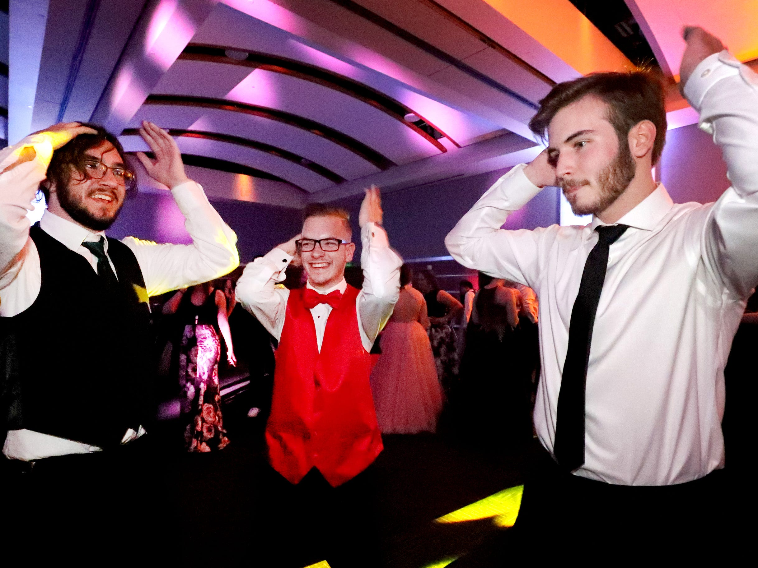(Left to Right ) Zach Wilder, Everett Davis and Zane Jones joke that the song goes on forever as they all dance the Macarena at Blackman's prom on Friday April 12, 2019, at MTSU.