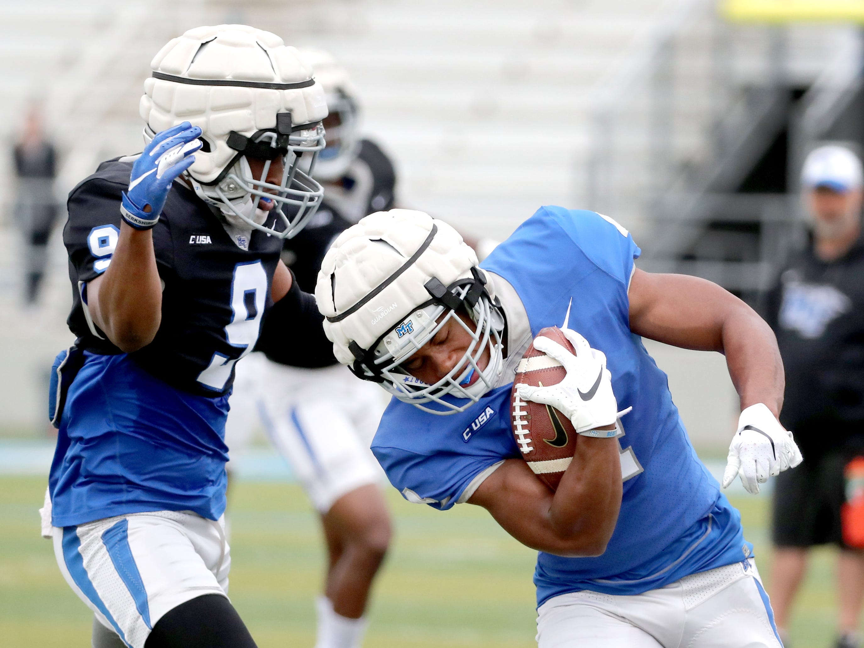 "MTSU's running back D'Monte Kemp (4) runs the ball as MTSU's safety Jourdan Sweet (9) moves in for a tackle during MTSU's Blue-White Spring Finale held on Saturday April 13, 2019, at MTSU's Johnny ""Red"" Floyd Stadium."