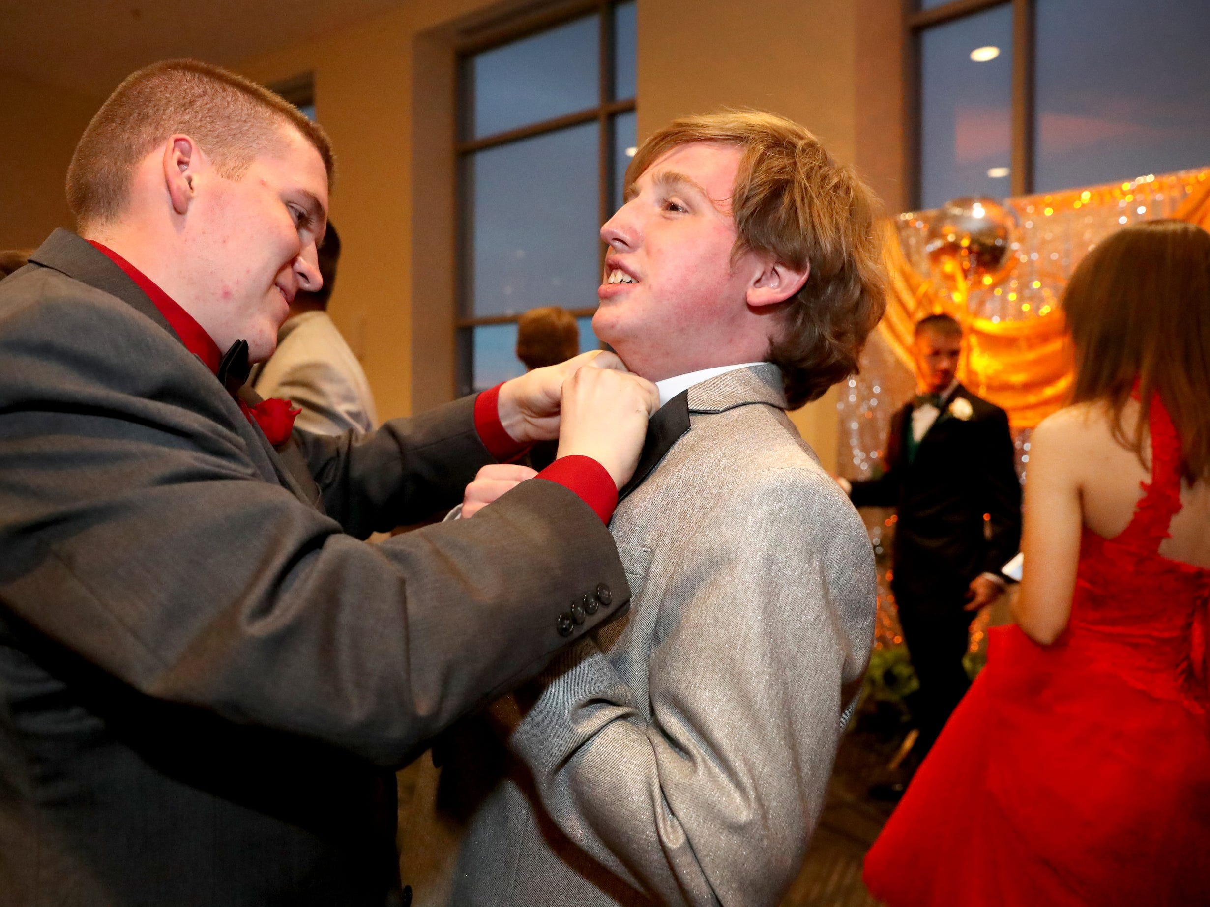 Allen Hoehne, left helps Benjamin Barnes with his tie at Blackman's prom on Friday April 12, 2019, at MTSU.